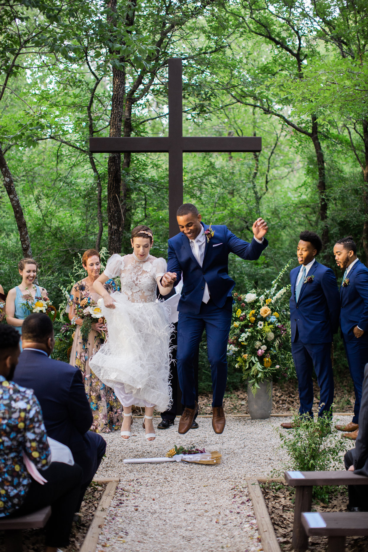 Bride and groom jumping over a broom while wedding party and guests watch