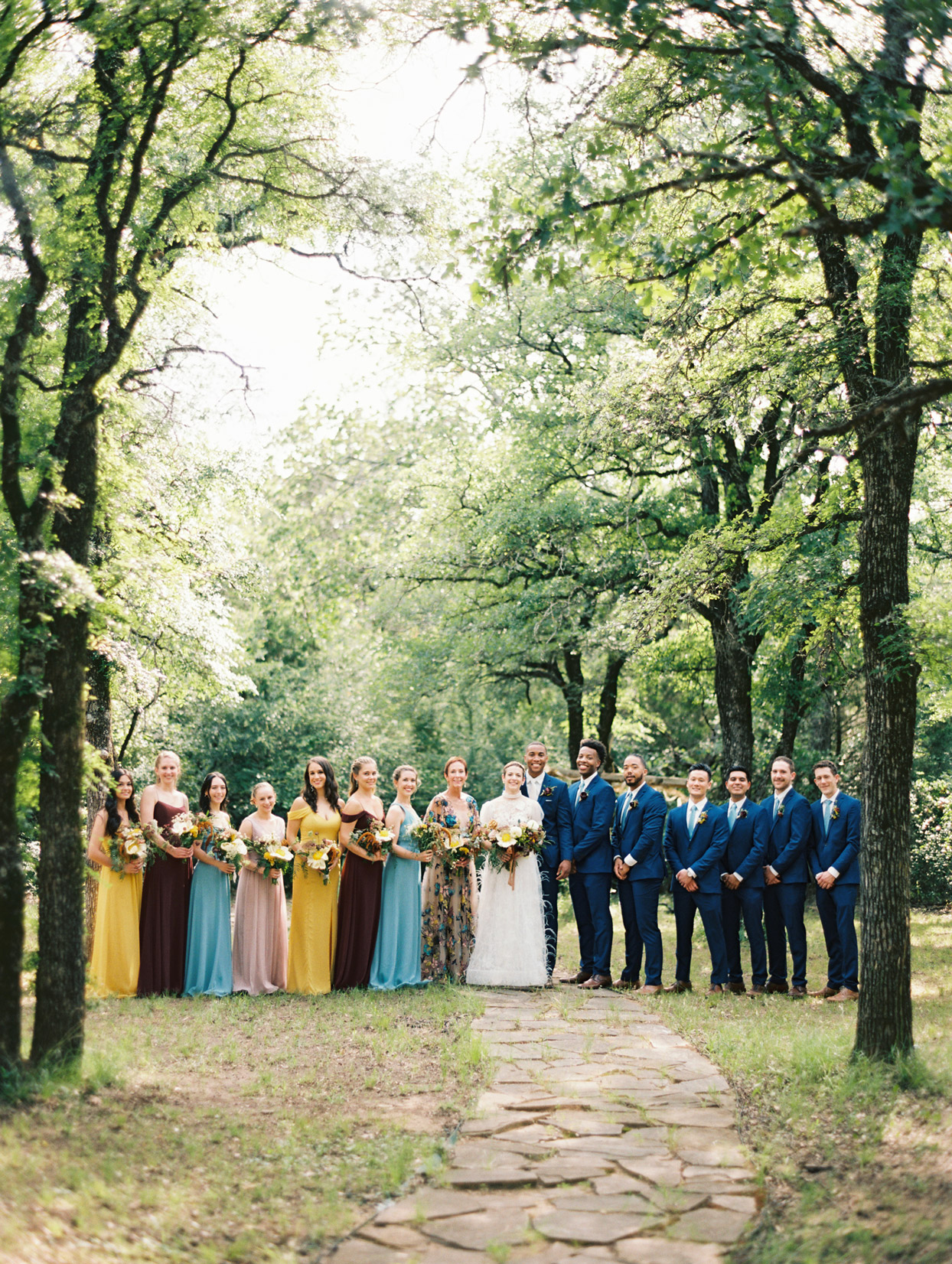 Wedding party posing on stone path in wooded area
