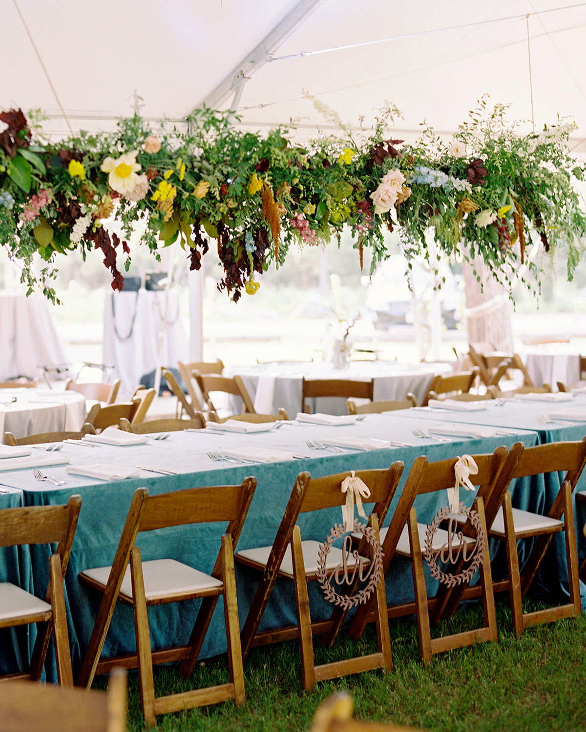 Picnic gazebo seating for wedding with folding chairs and long floral arrangement