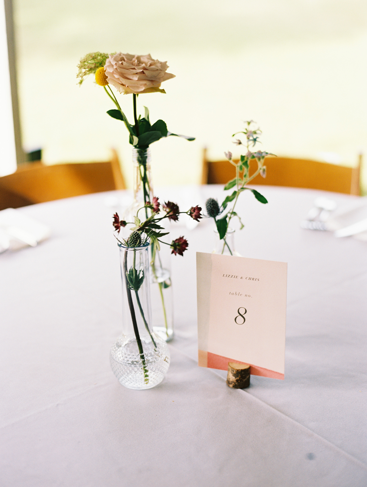 Table with white cloth with bud vases