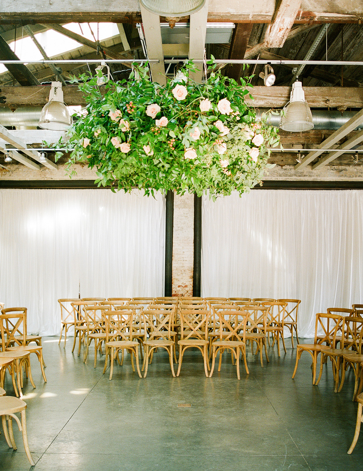 shelby david wedding industrial ceremony space with floral hanging
