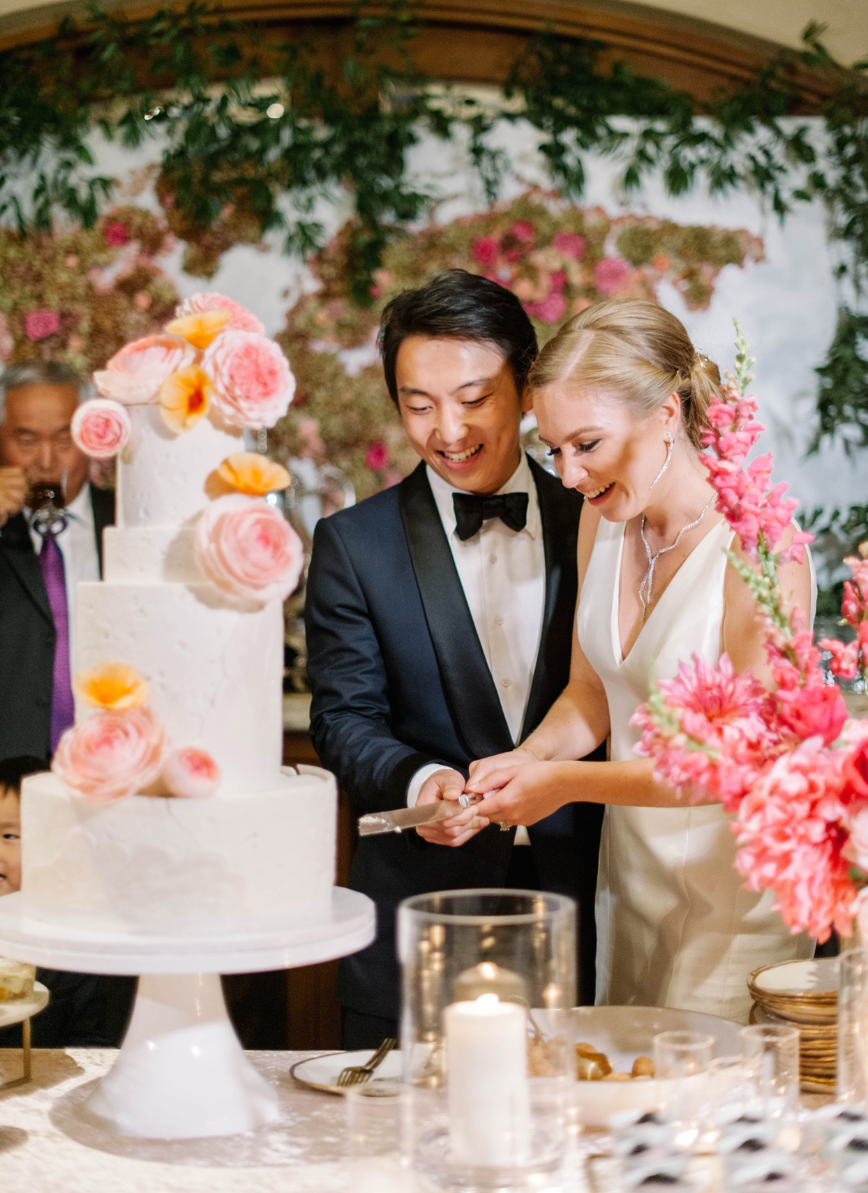 bride and groom cutting floral wedding cake