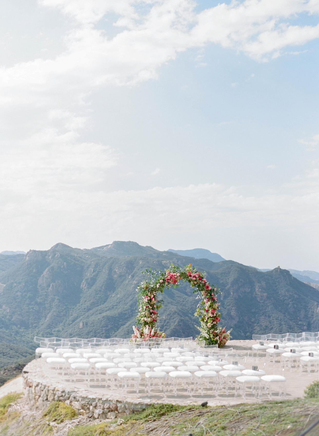 rose and dahlia floral arch and ceremony chairs overlooking mountains