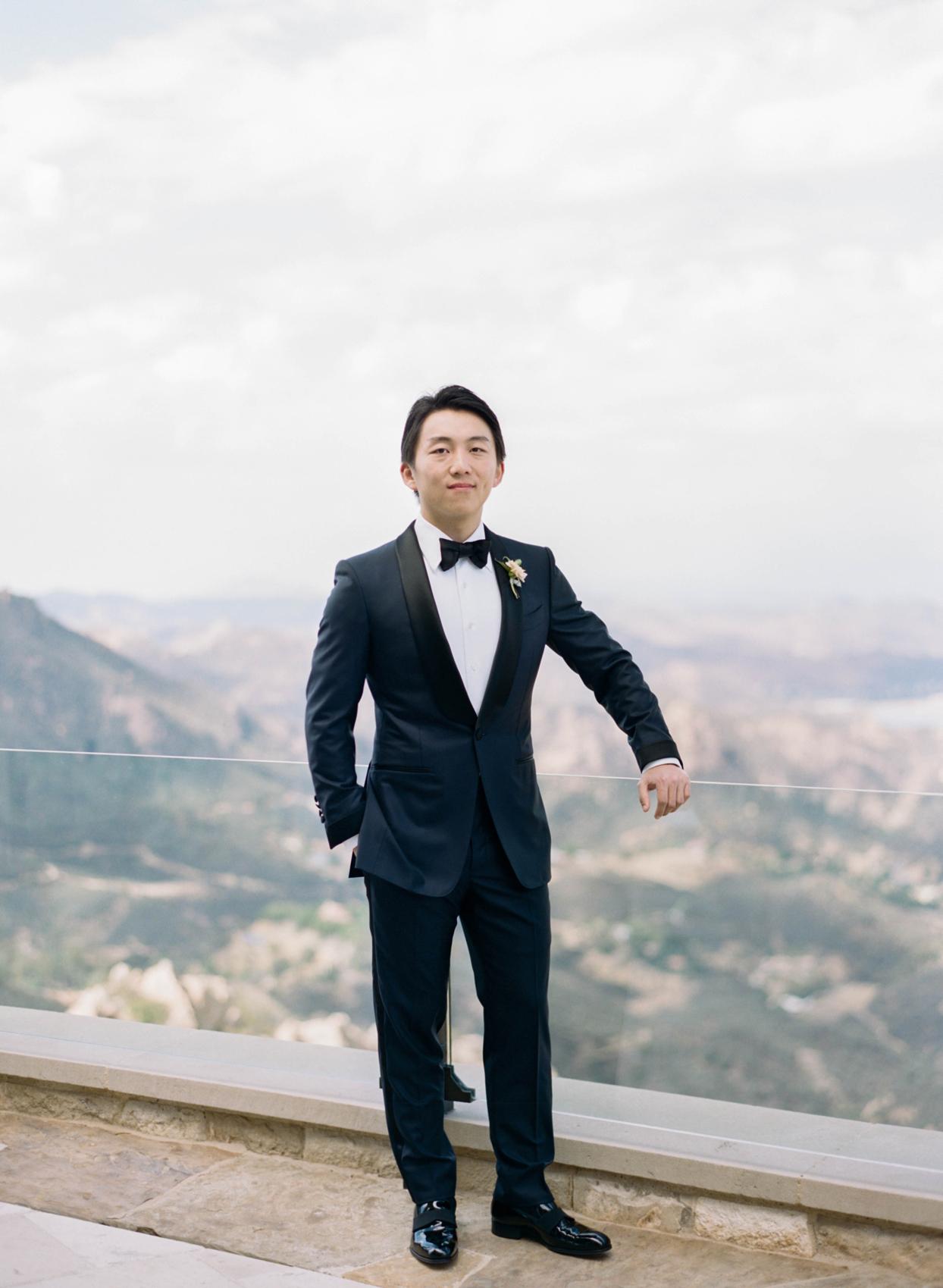 groom wearing tuxedo posing on balcony