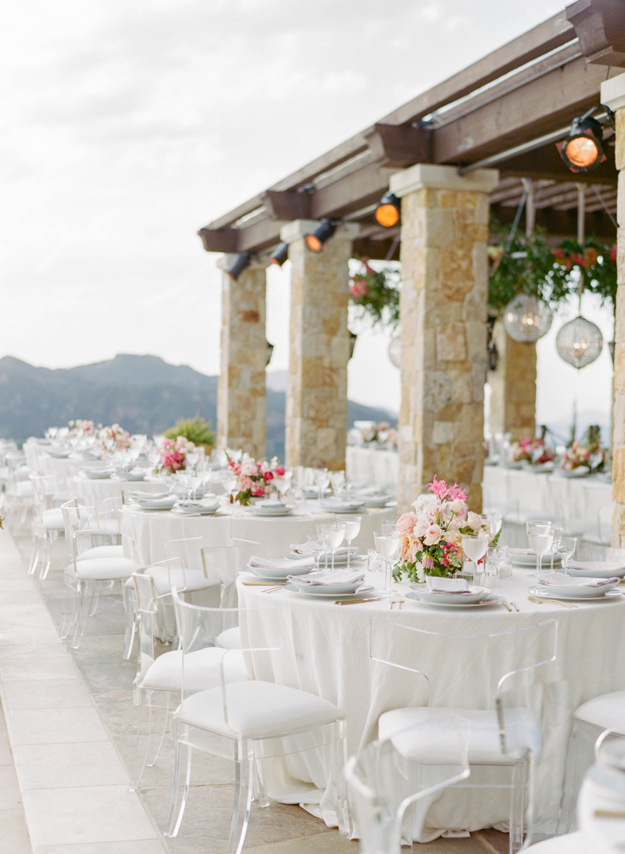round reception tables adorned with pink floral centerpieces overlooking mountains