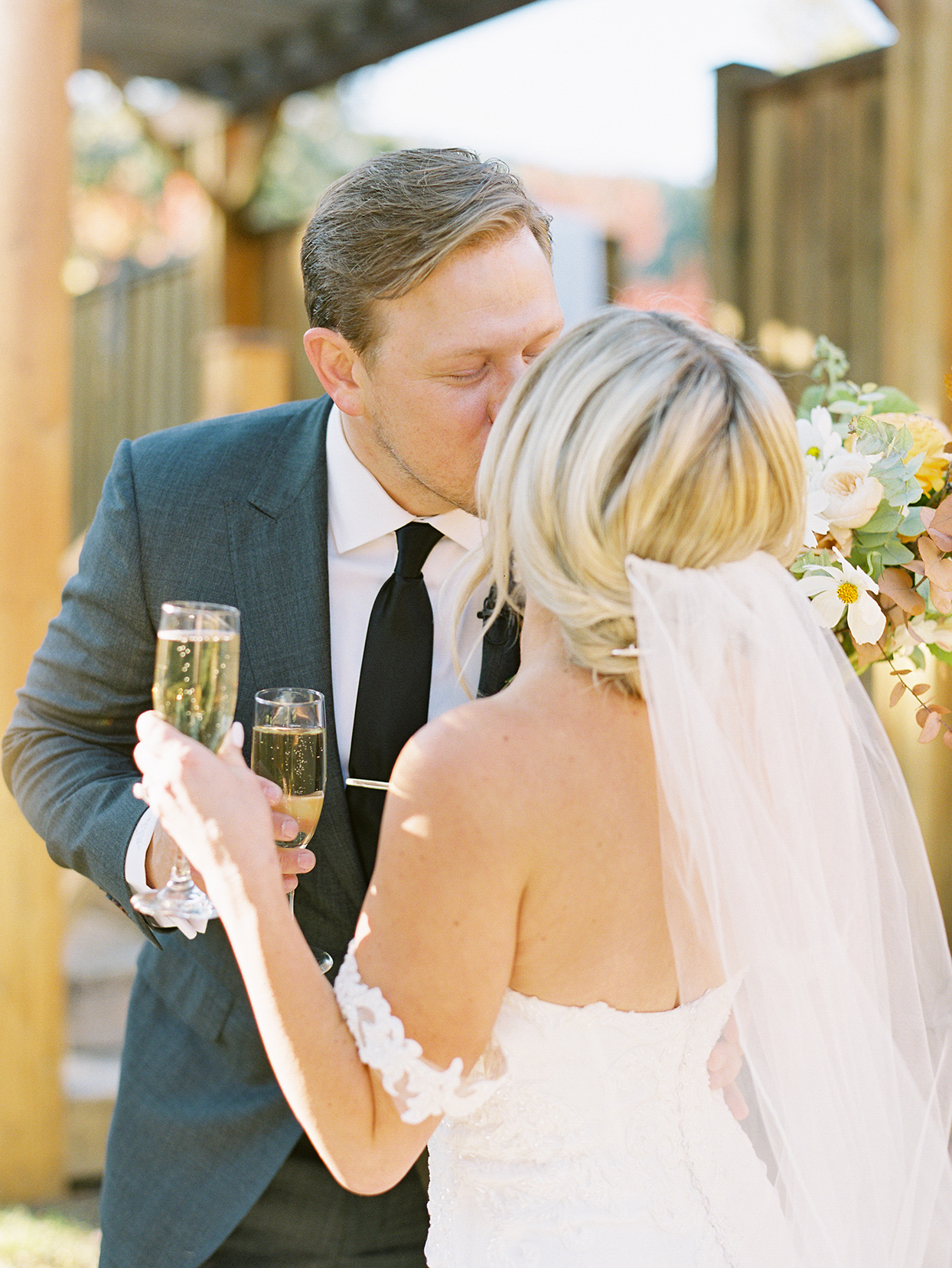 alexandra david wedding couple kissing with champagne