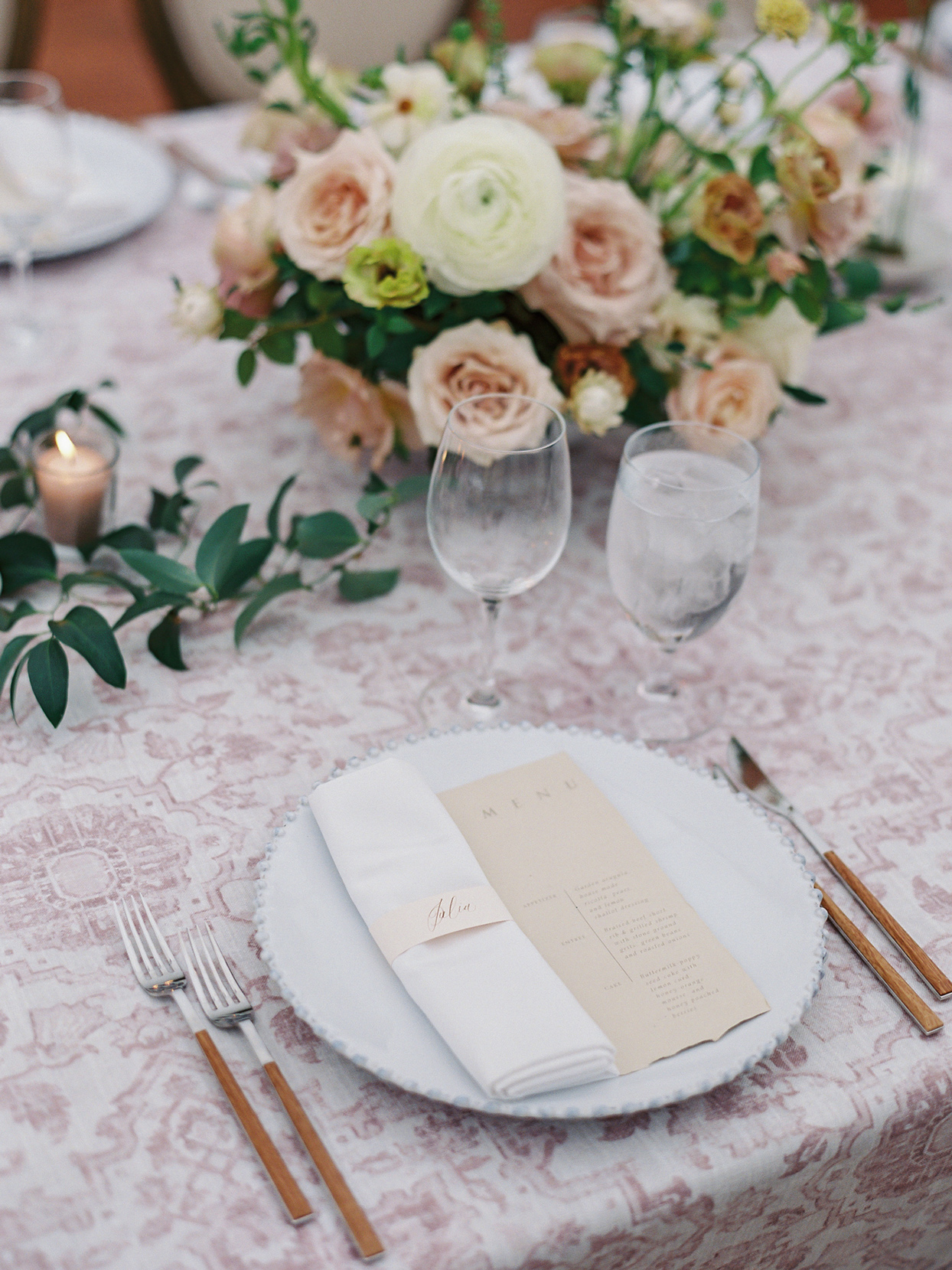 Wedding place setting with patterned linens paired with white napkins
