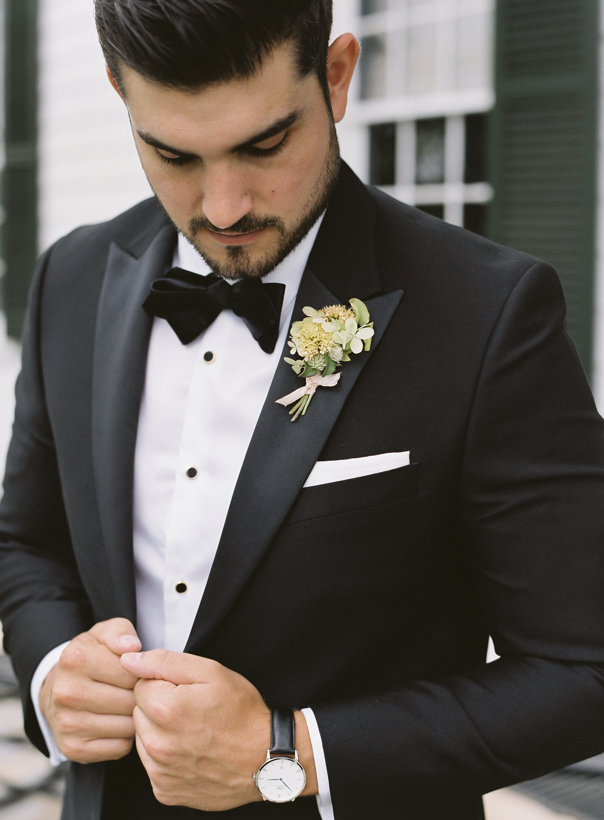 Groom in tux from The Black Tux featuring black bow tie, black studs, and a crisp white pocket square