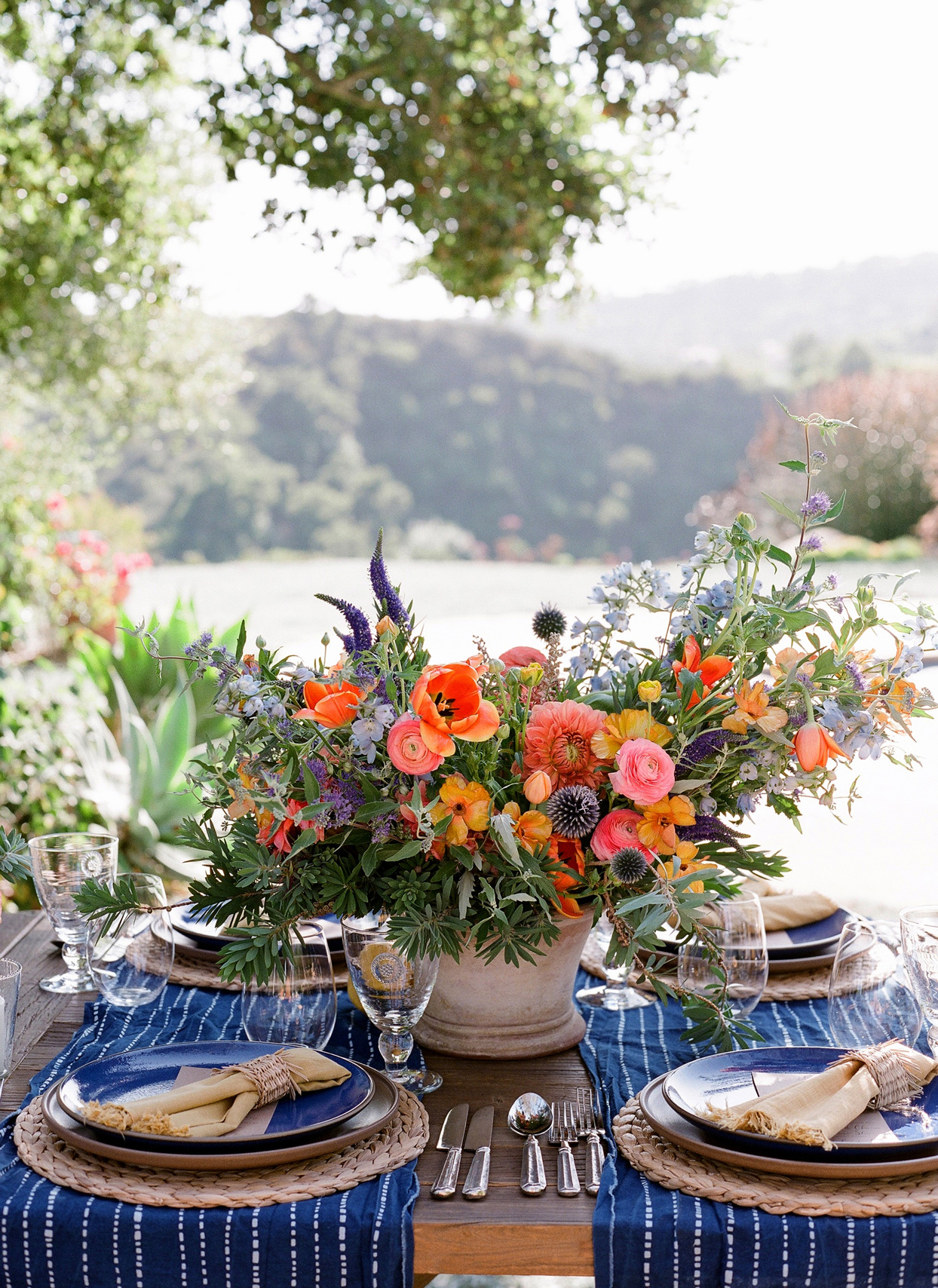 multicolor floral wedding rehearsal dinner centerpiece on wooden table with blue and white linens