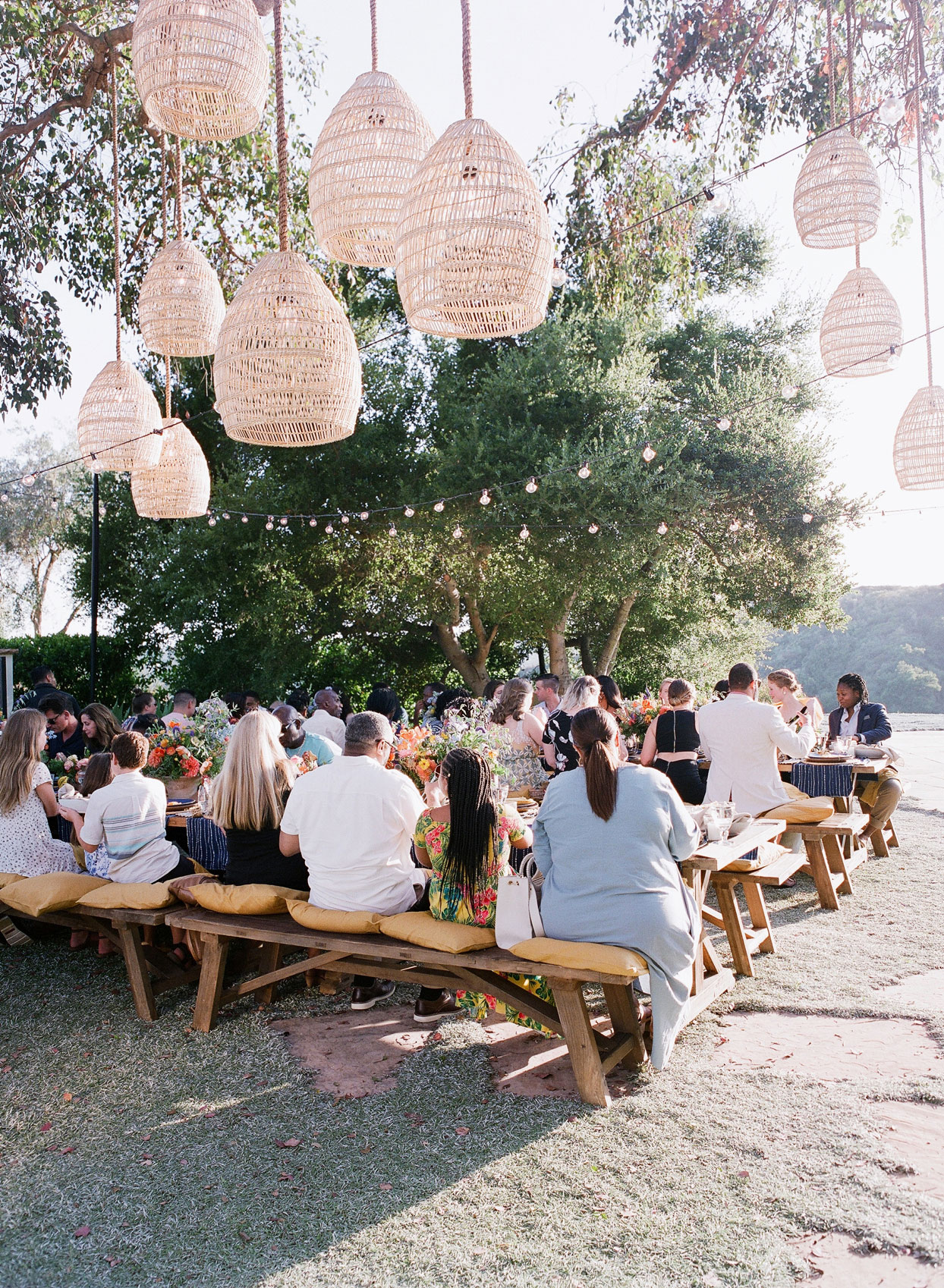 outdoor rehearsal dinner long wooden tables and benches with pillow cushion seating