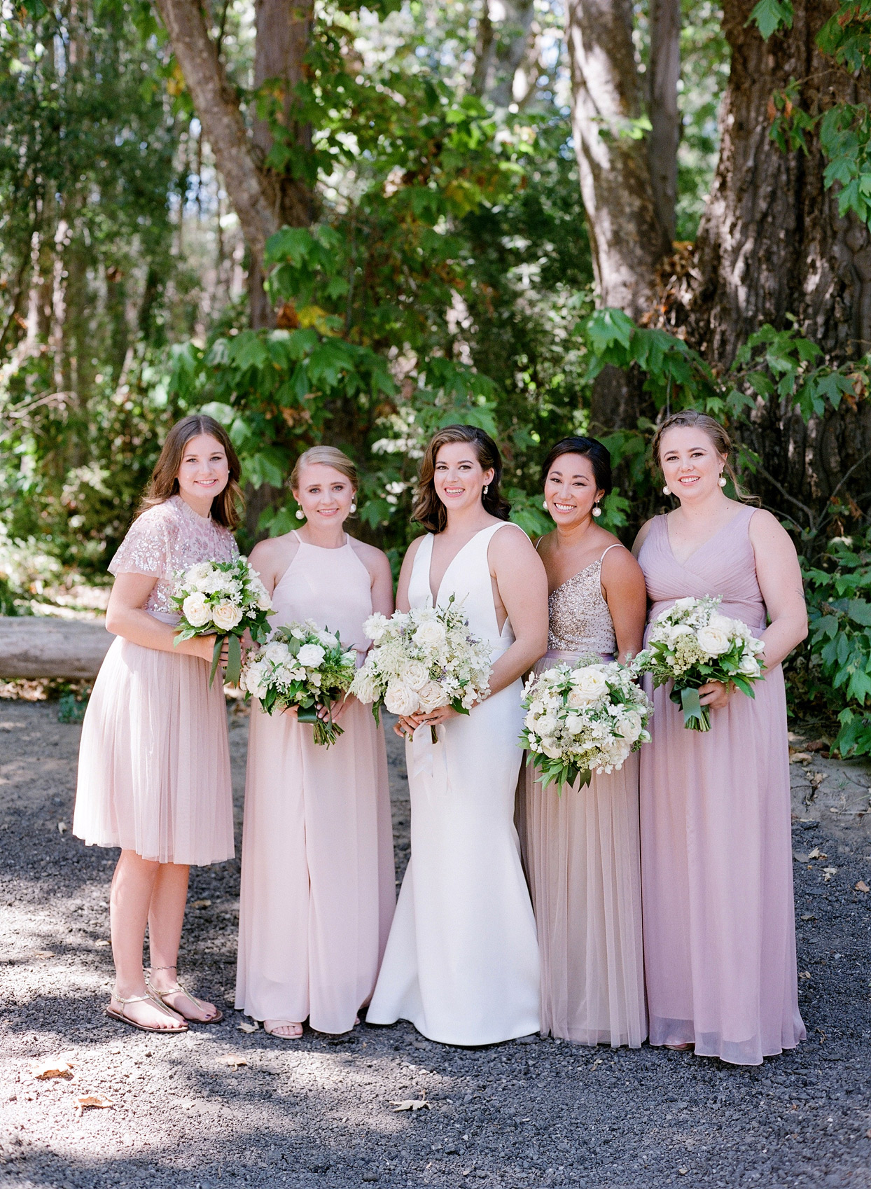 bridesmaids in various styled blush dresses standing with bride in wedding dress