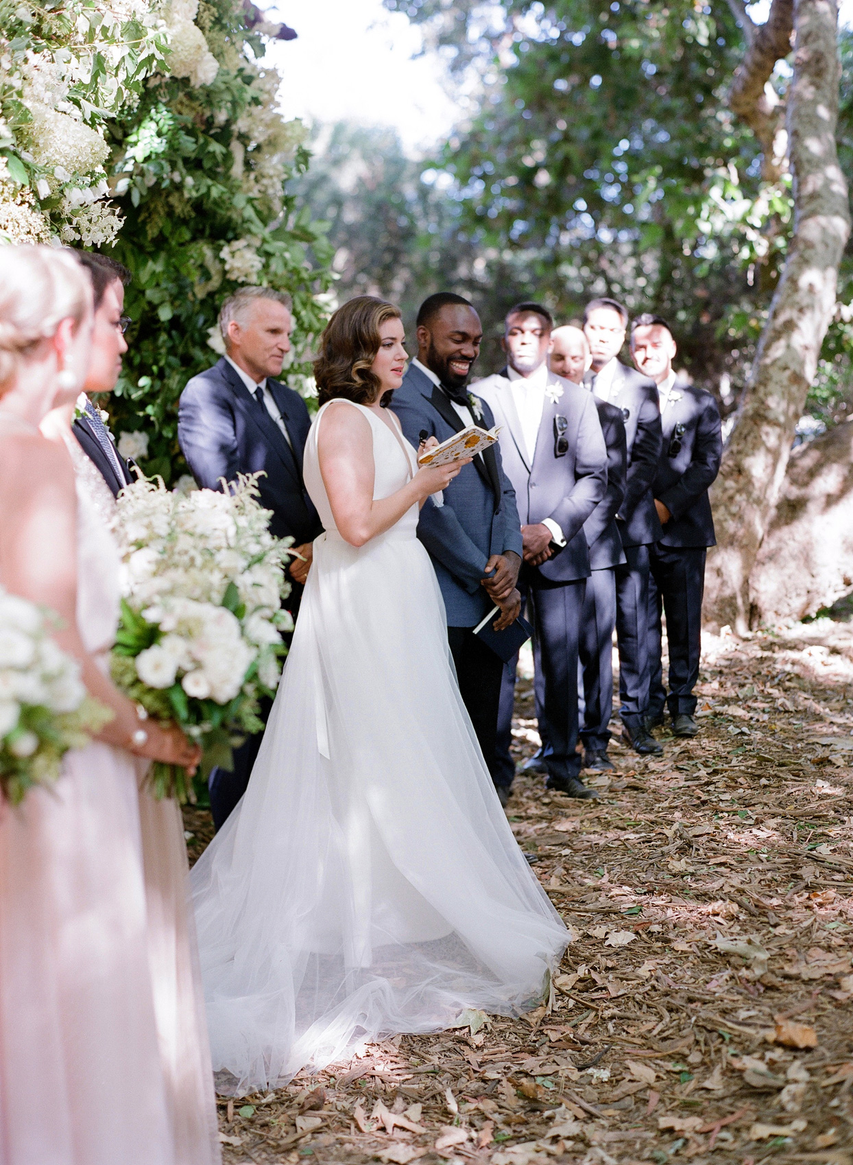 bride and groom reading vows during outdoor wedding ceremony