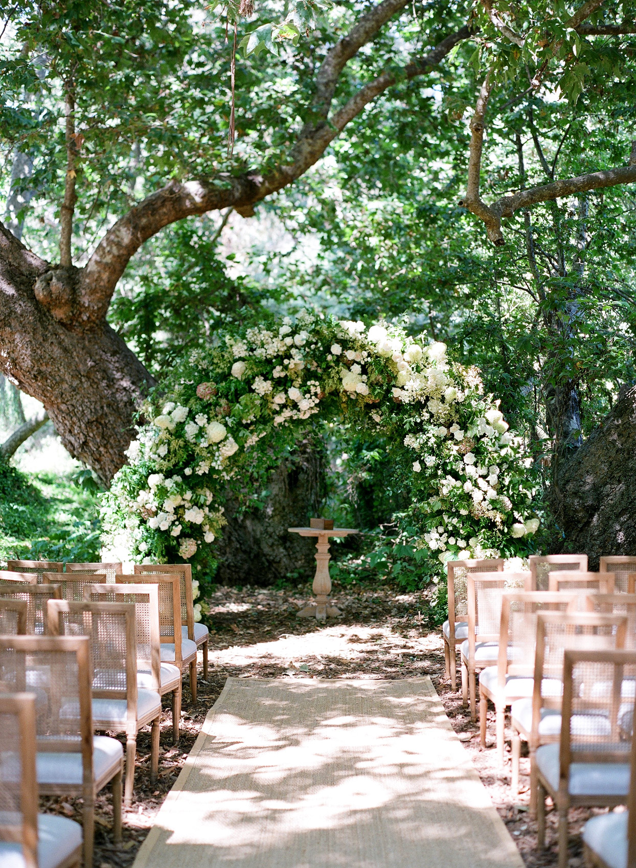 large white floral wedding arch for outdoor wedding ceremony
