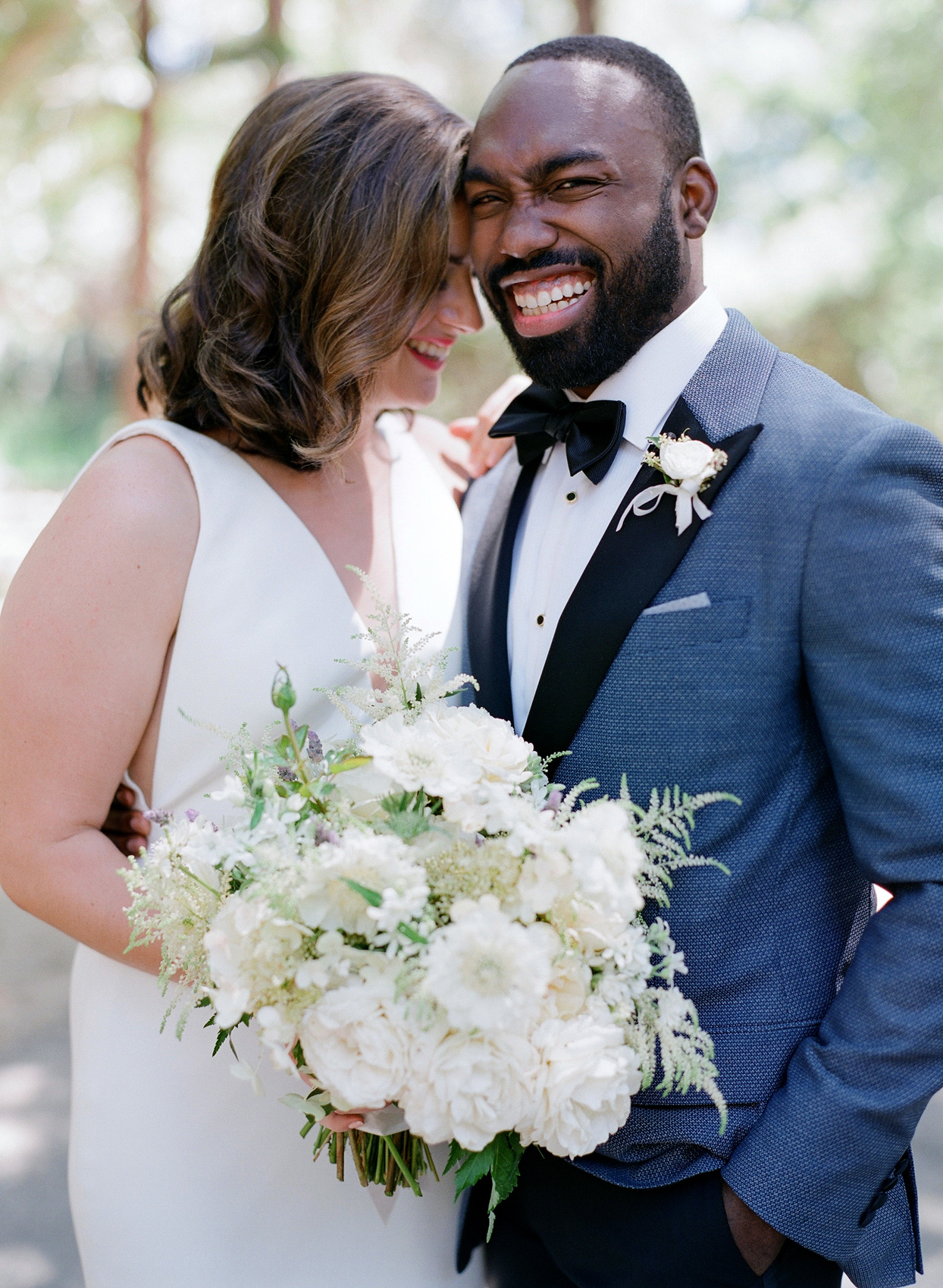 bride and groom smiling and laughing for wedding portrait photo outside