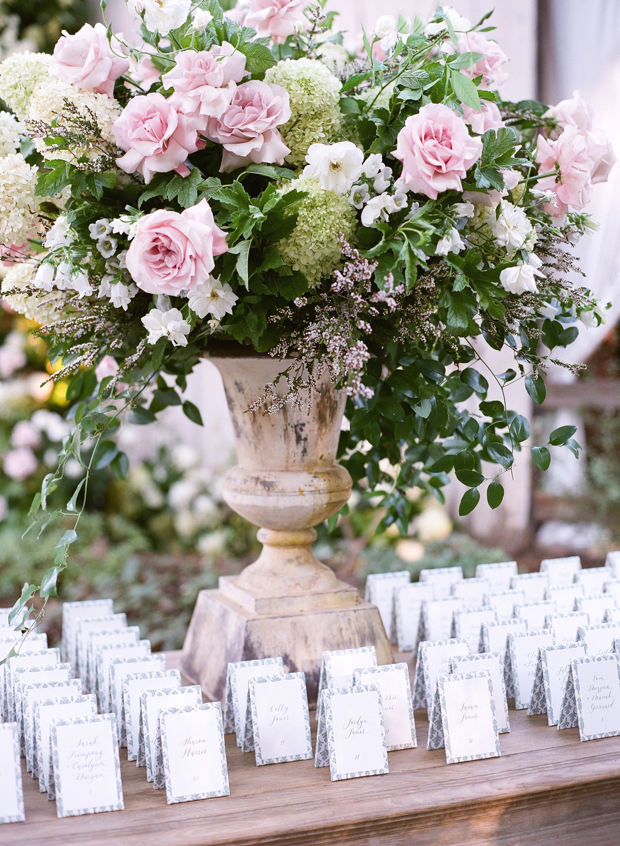 wooden table lined with white escort cards and pink floral arrangement