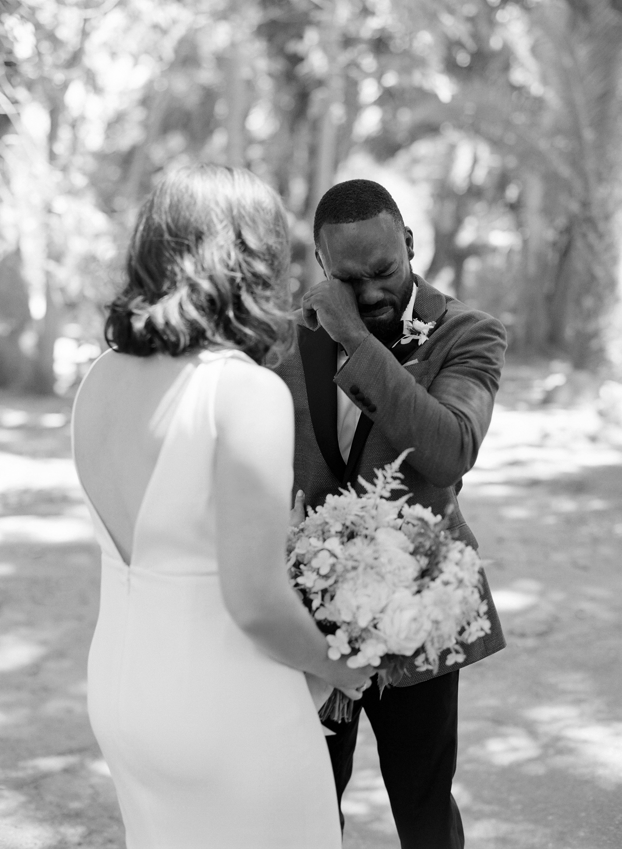 groom wipes away tear during first look with bride