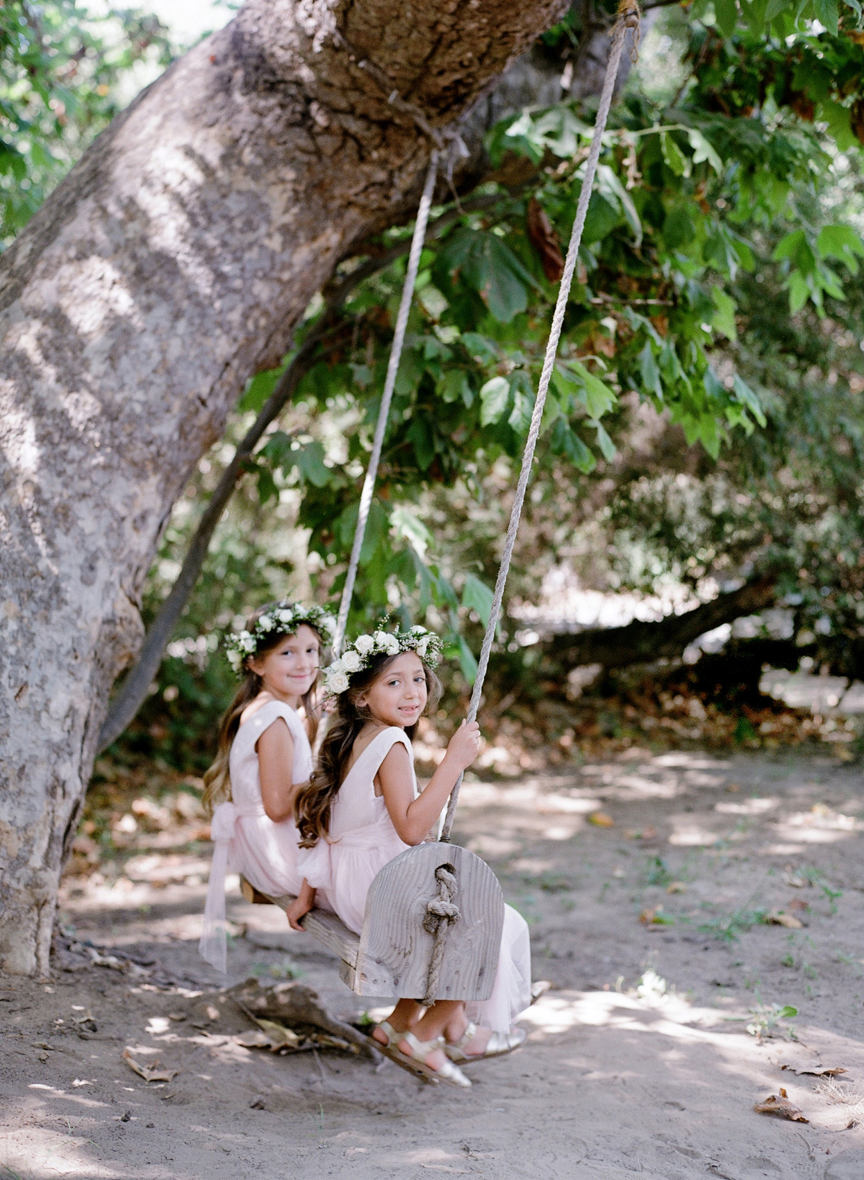 flower girls wearing floral crowns sitting on wooden swing hung from tree