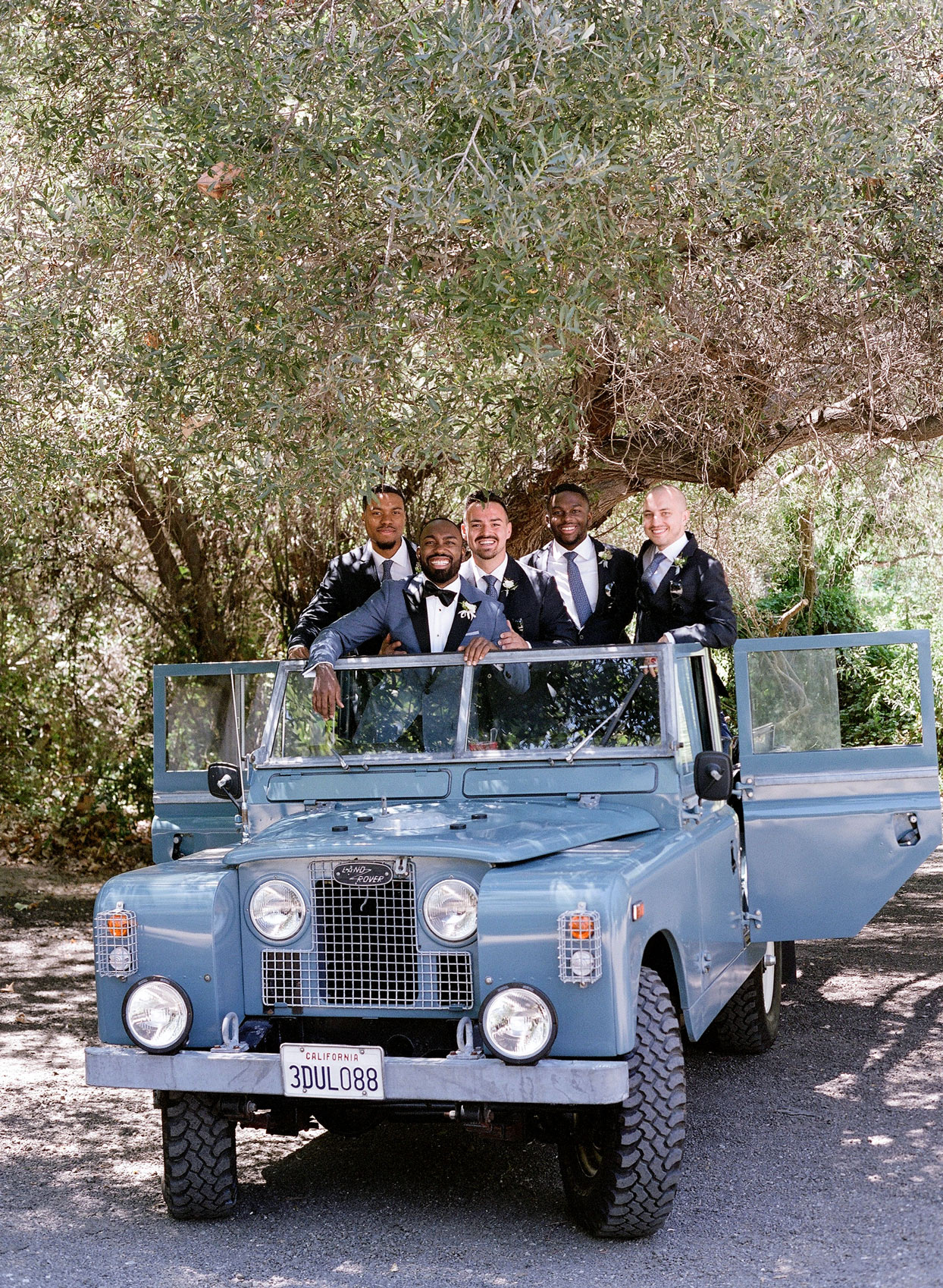 groom with groomsmen in blue-gray jeep