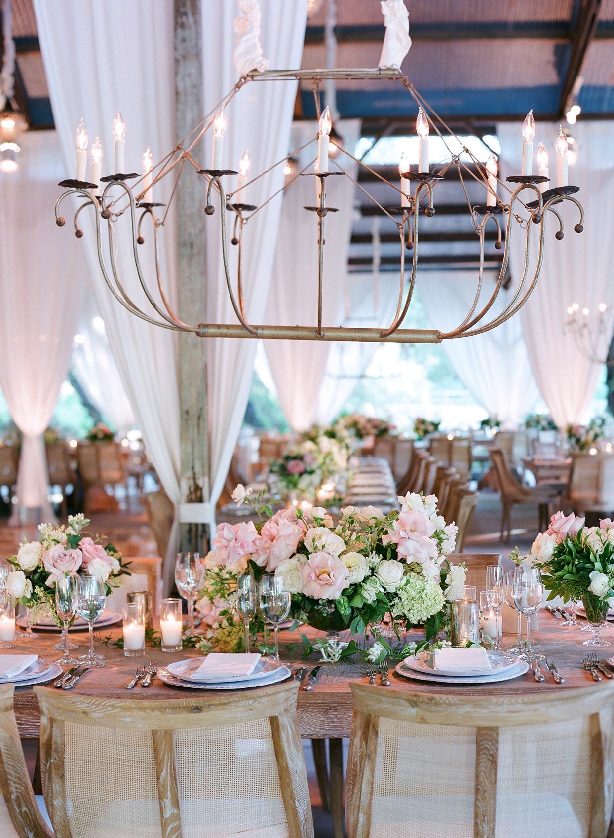 pink and green floral centerpieces and glass holders with candles reception table decor