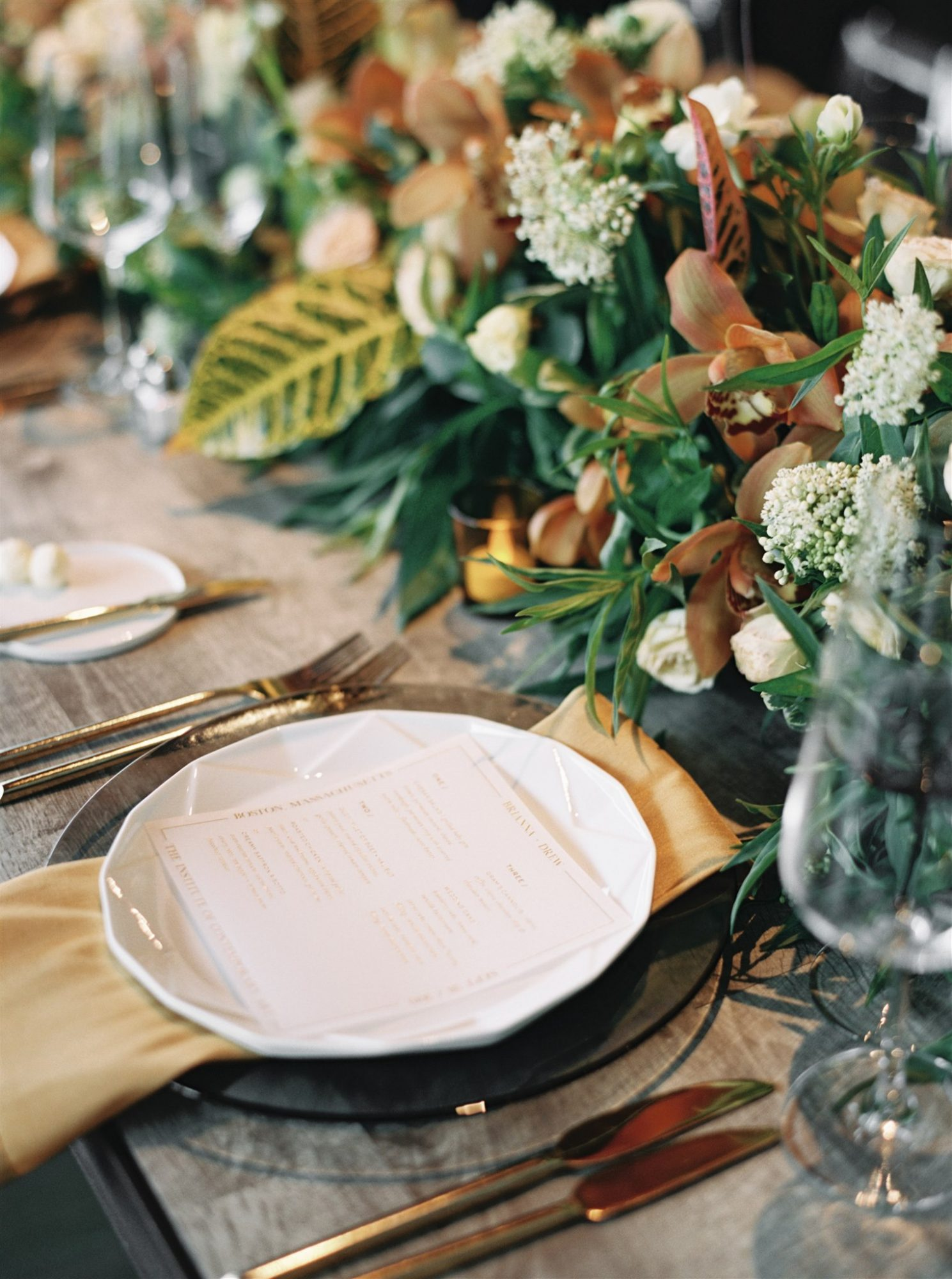 wedding place setting black white and amber on rustic wood table