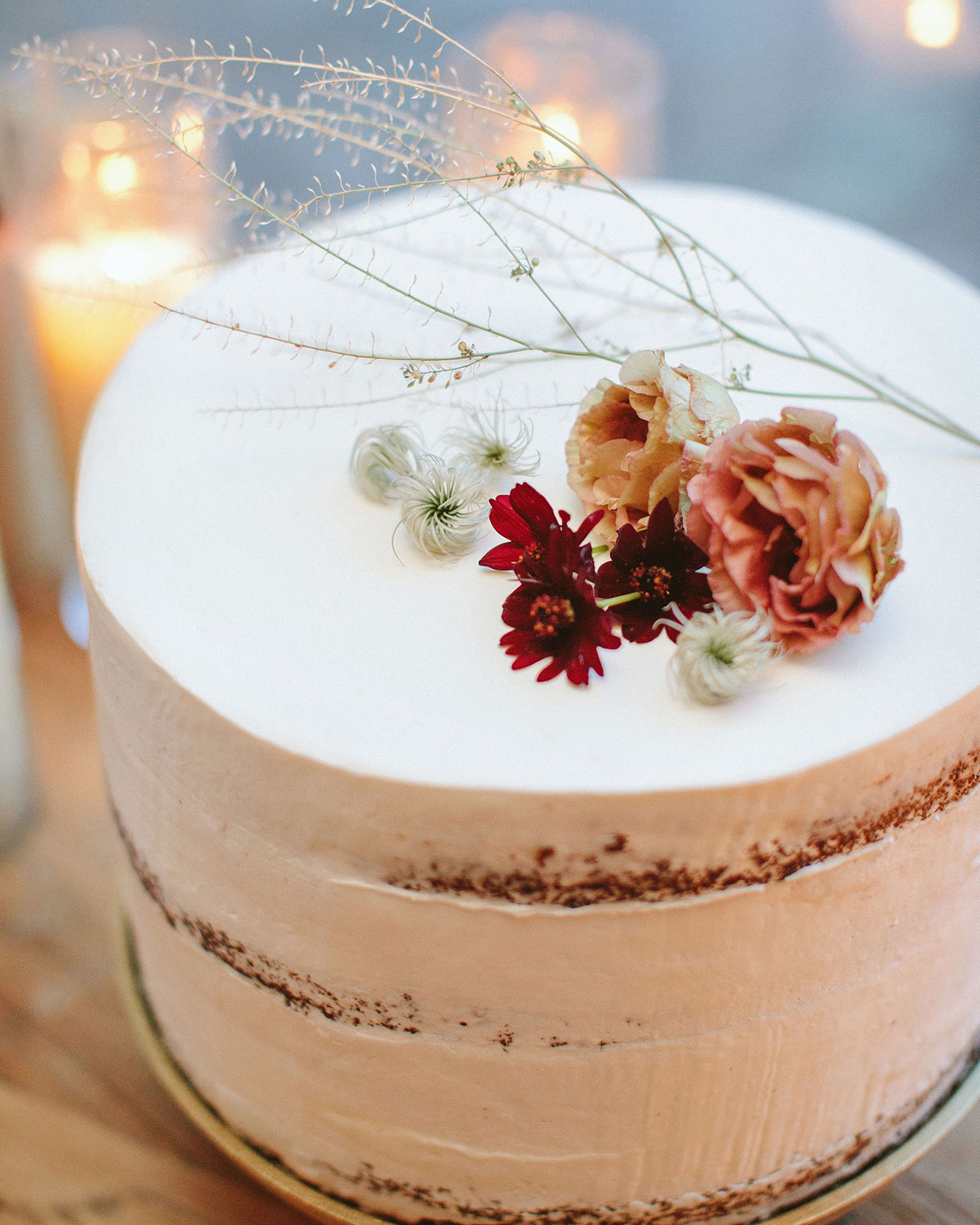 clare tim simple nearly naked wedding cake with red tones flowers
