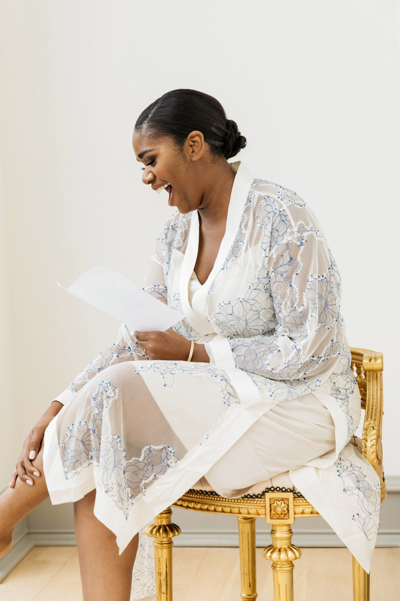 sitting bride laughing while reading a card
