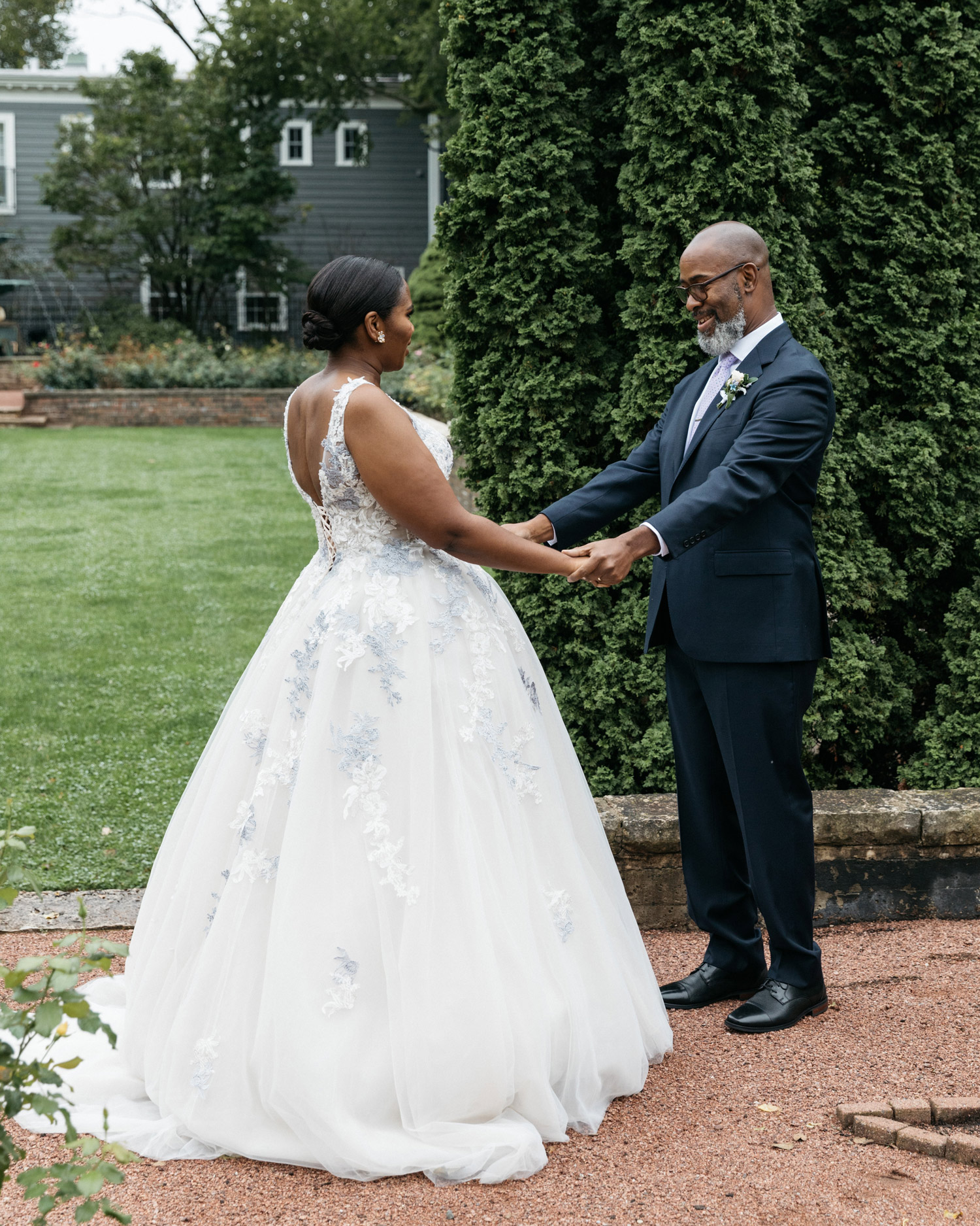 bride facing father holding hands outdoors
