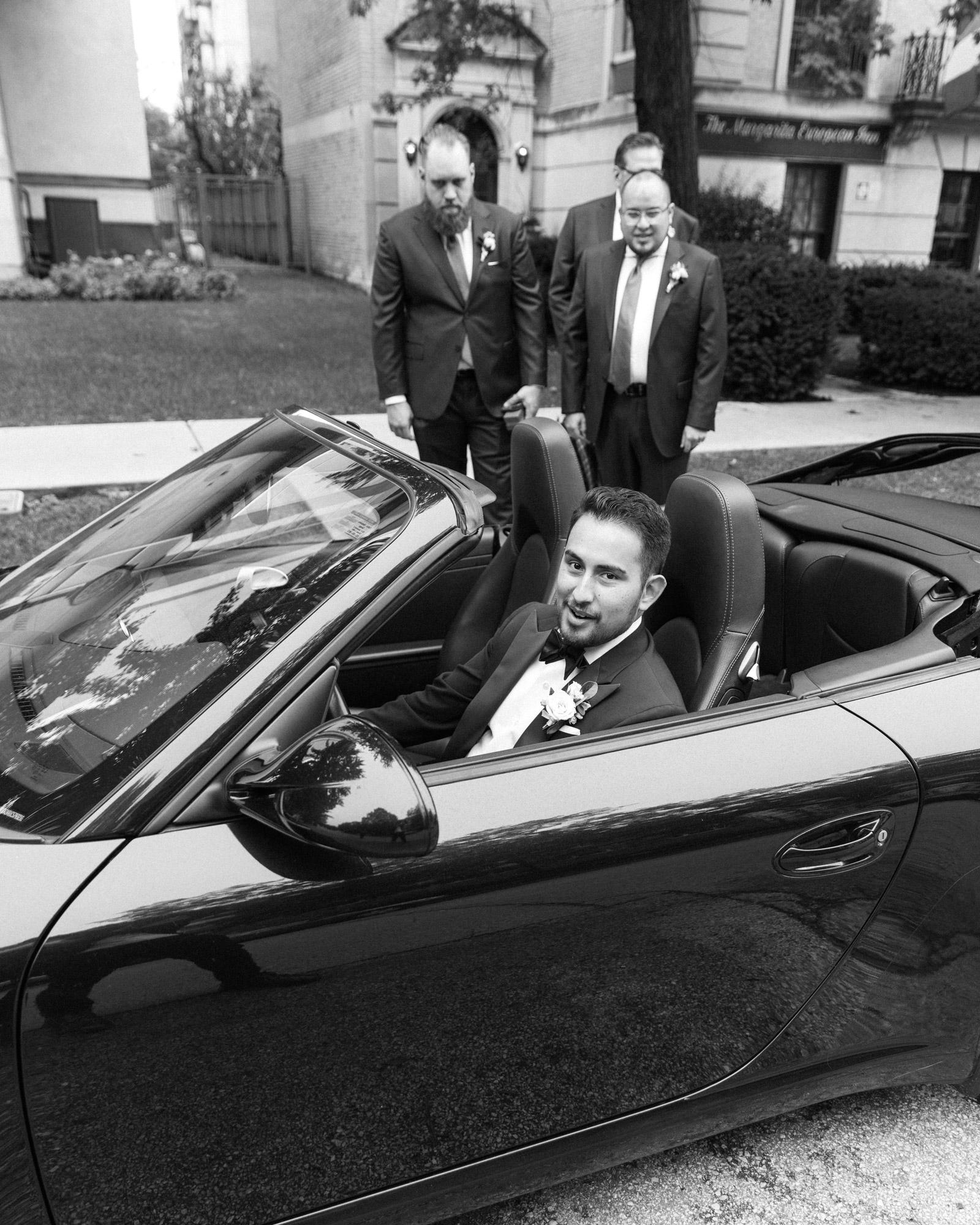 black and white groom in car groomsmen standing behind