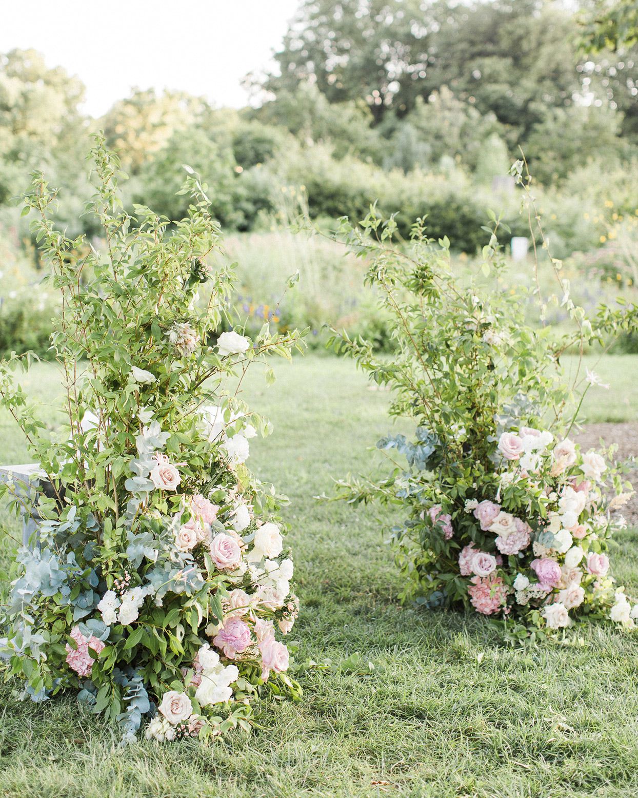 grace john wedding ceremony floral arrangements creating ceremony arch in grass
