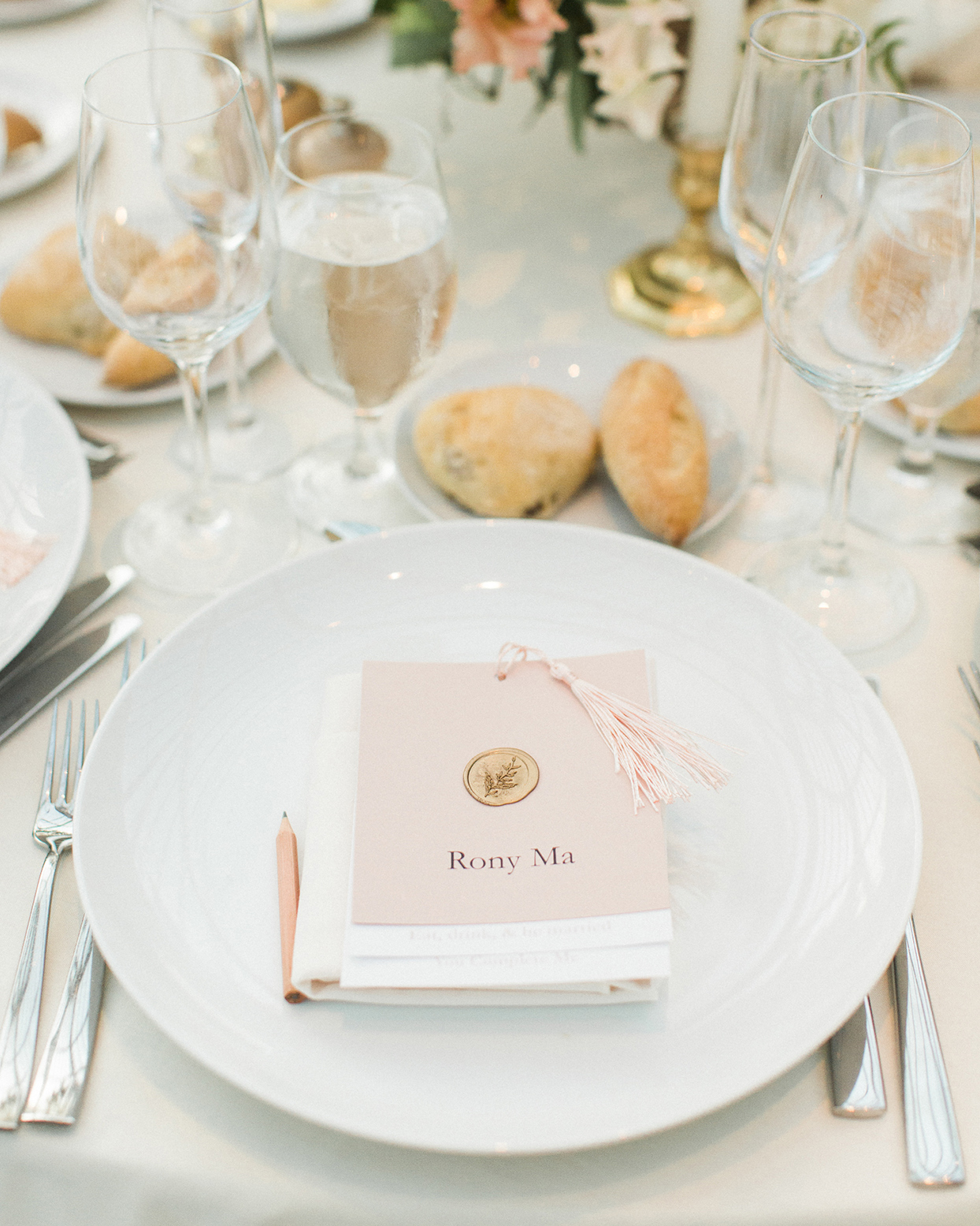 grace john wedding place setting with pastel pink place card on plate