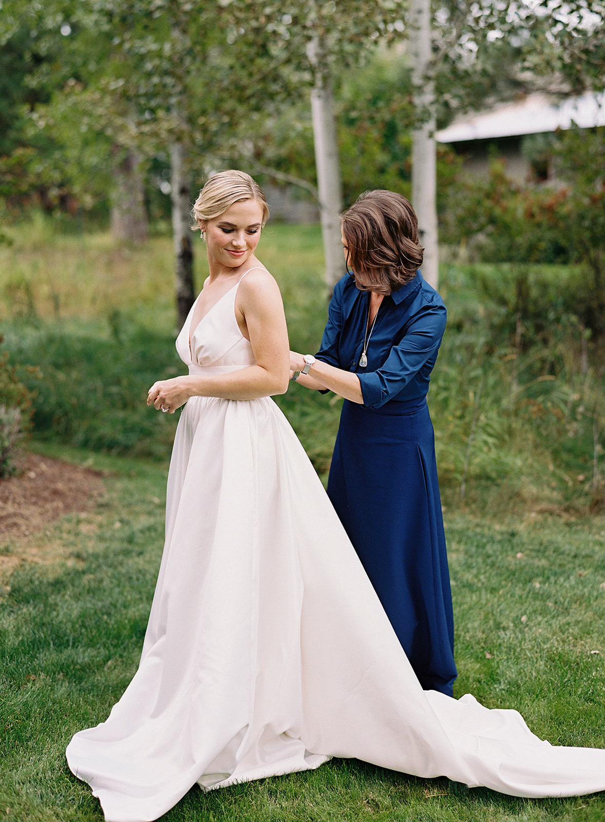 bride receiving help with finishing touches closing wedding dress outside