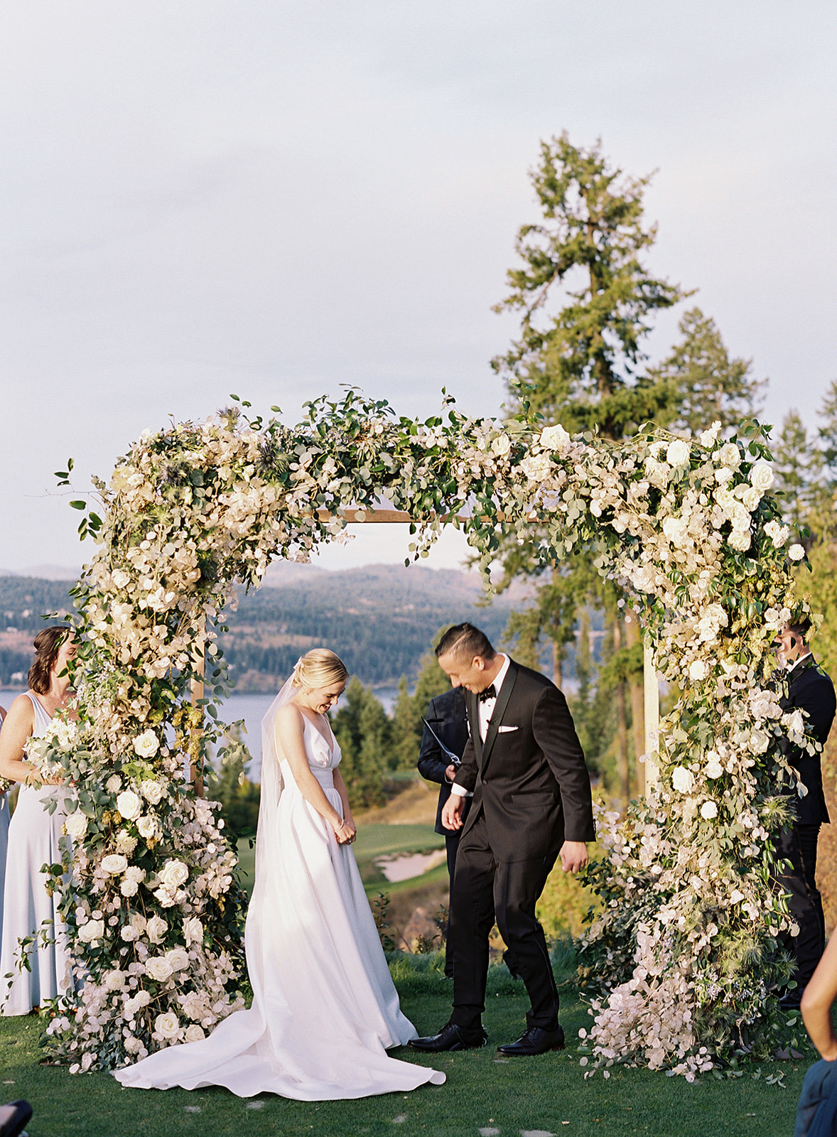 bride and groom next to floral wedding arch outside