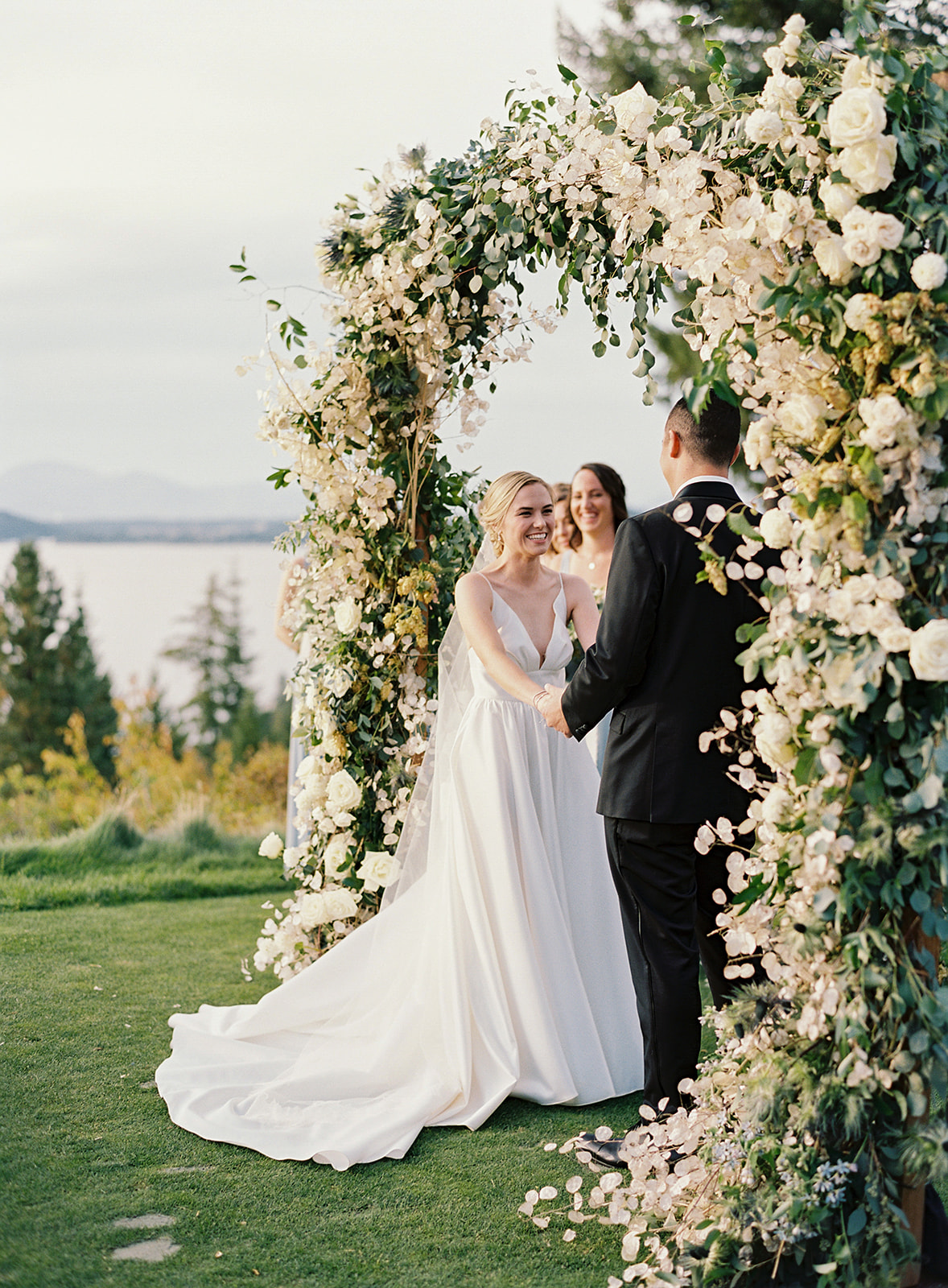bride and groom holding hands smiling under floral wedding arch
