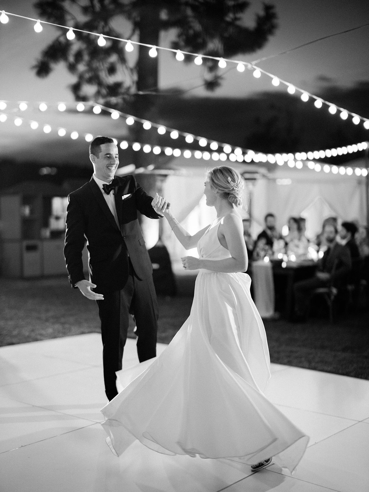 bride and groom smile during first dance on outdoor dance floor