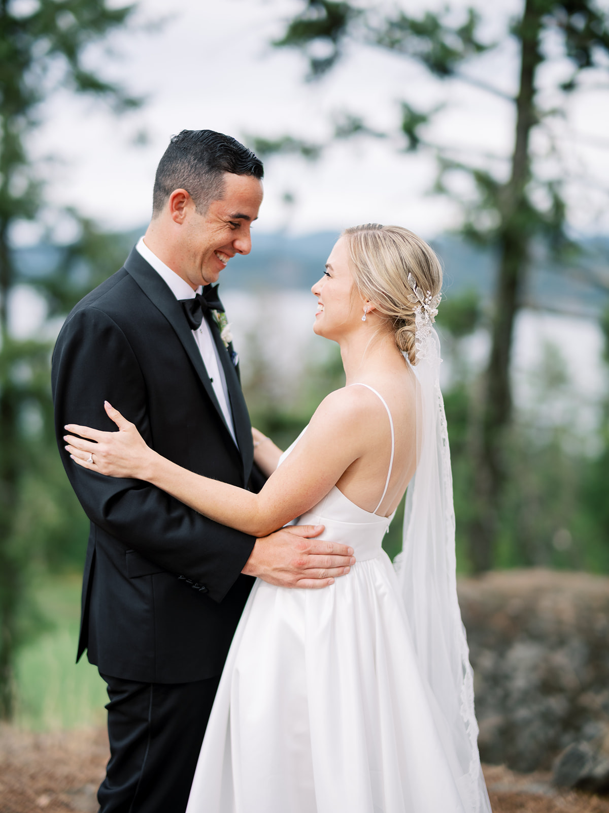 bride and groom embrace smiling outside during first look