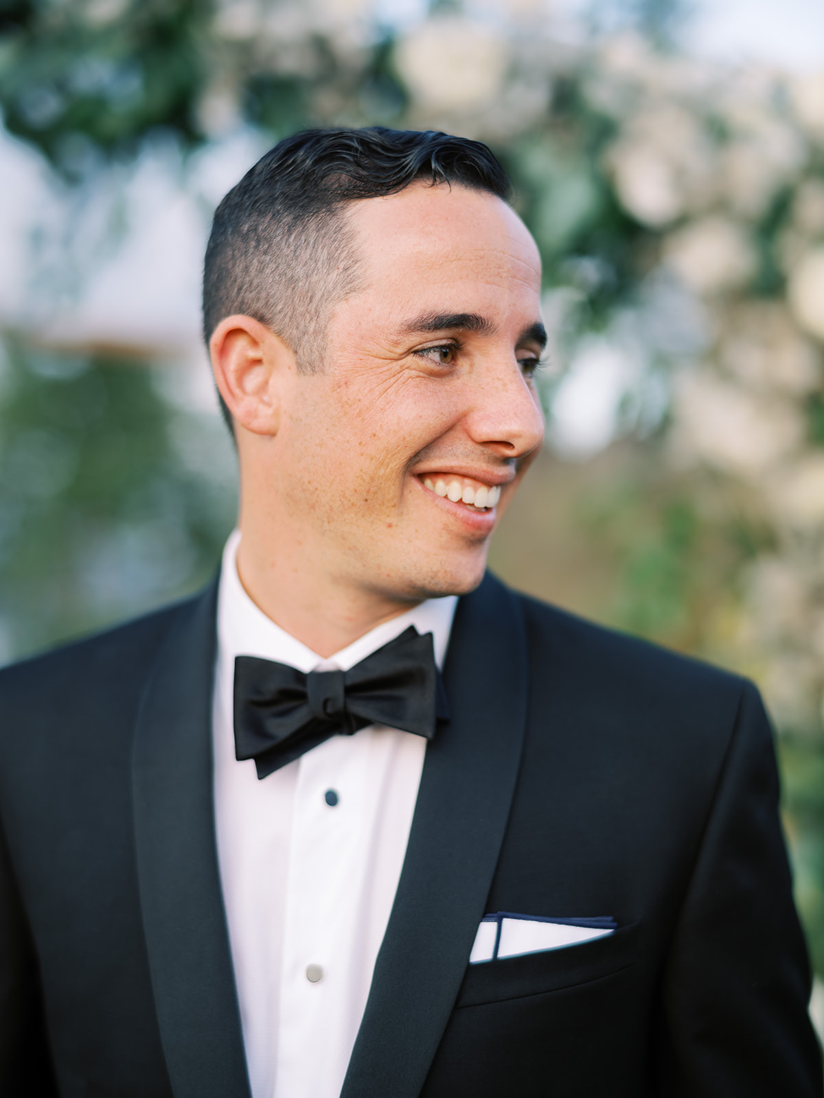 groom wearing traditional black and white tux with bow tie