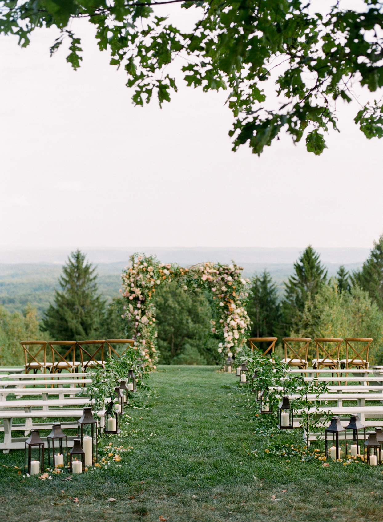 ceremony space decorated with hanging lanterns and a floral arch