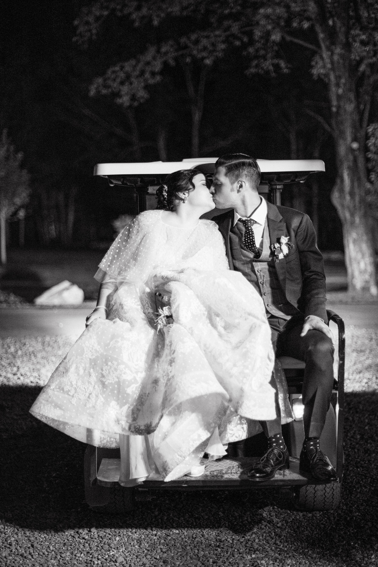 bride and groom kissing behind wedding golf cart