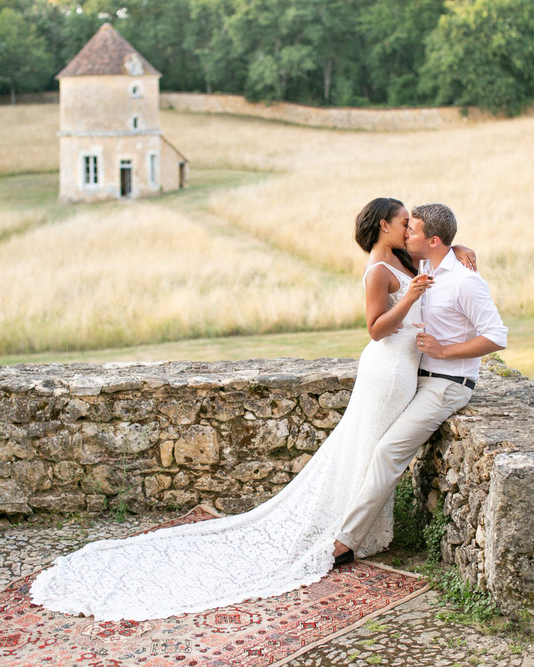jen tim wedding couple kissing against stone wall