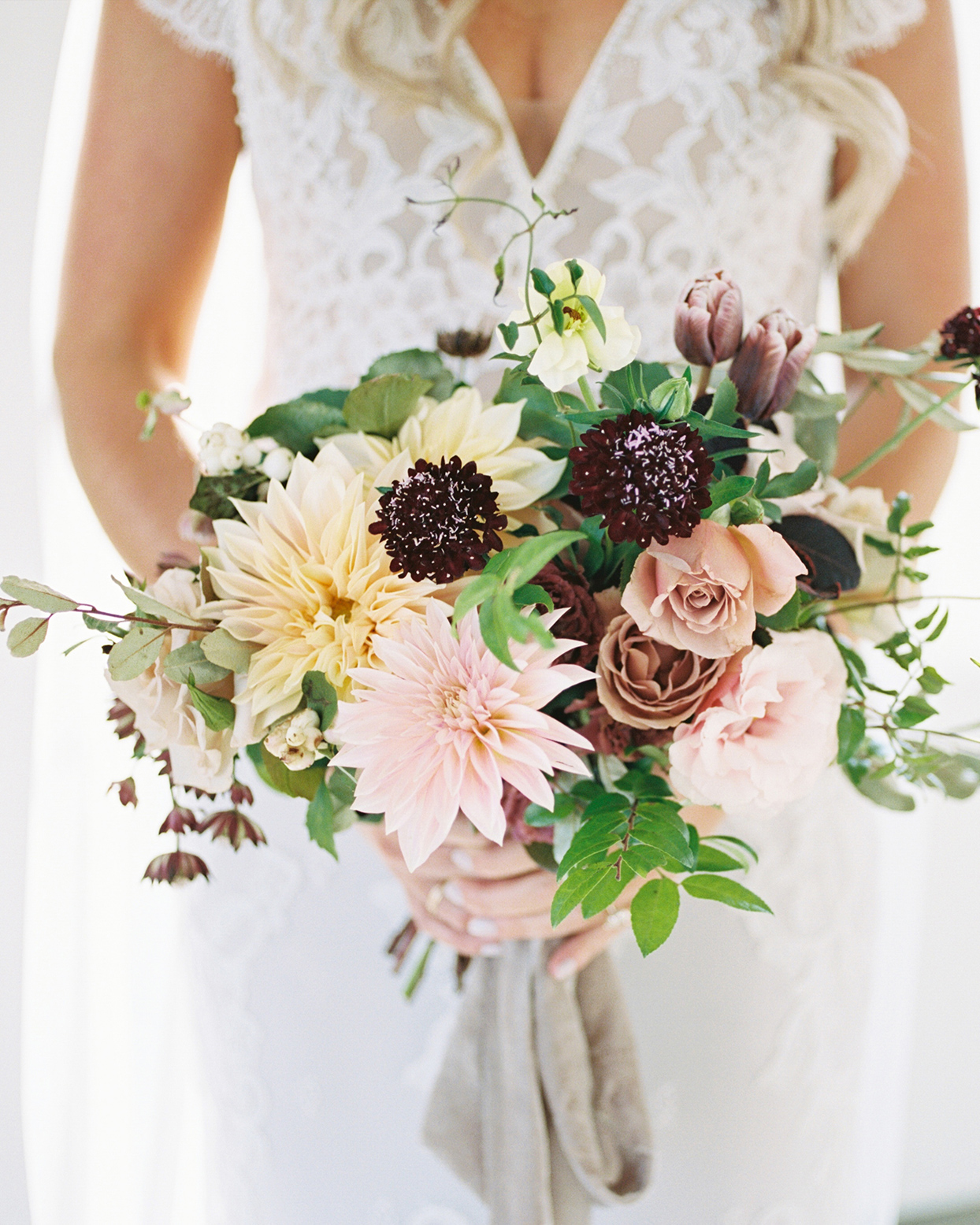 bouquet with cafe au lait dahlias, garden roses, blush lisianthus, butterfly ranunculus, and black scabiosa in neutrals and pale pinks