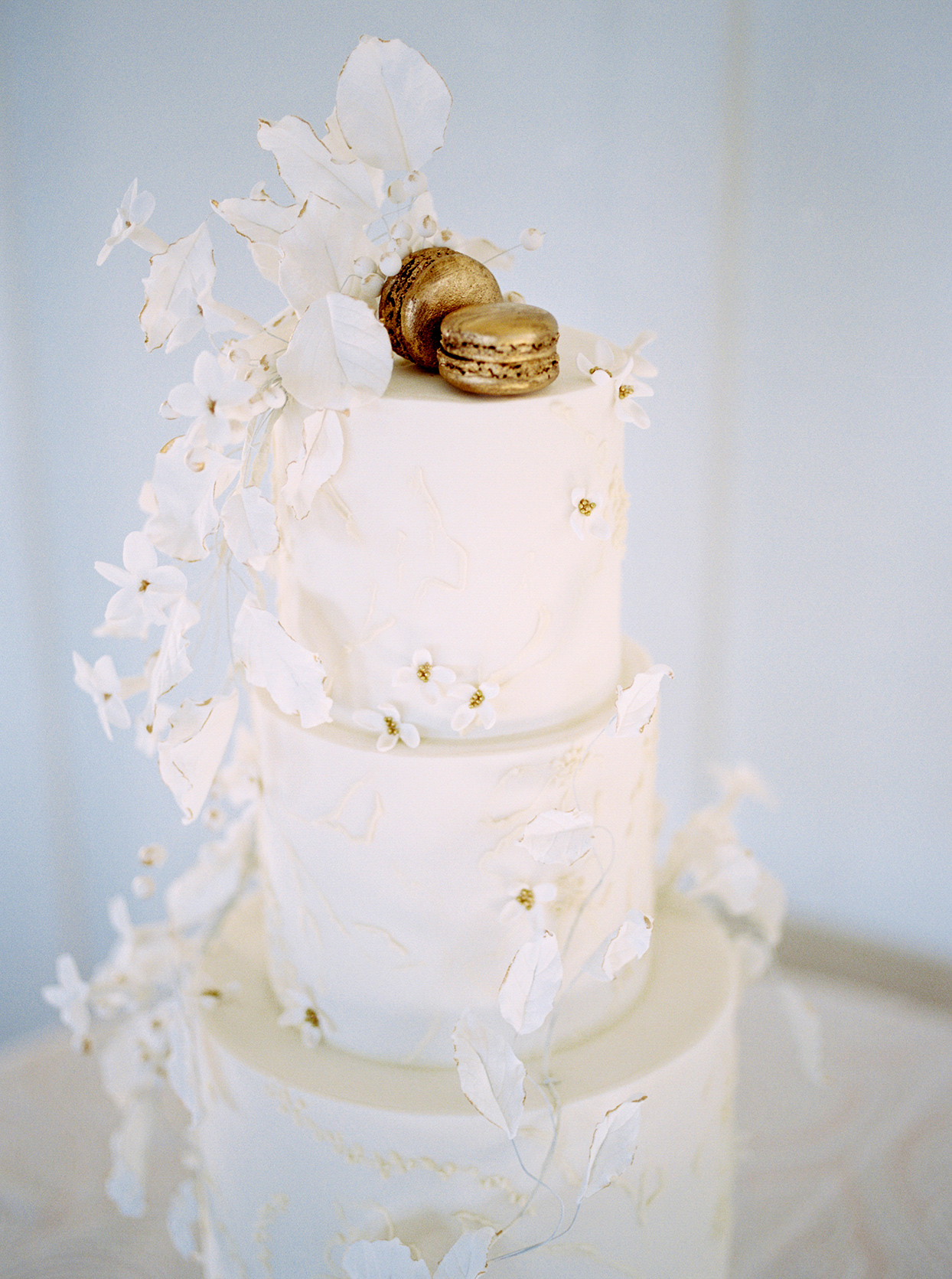 White wedding cake from Miam Cake with gold macarons