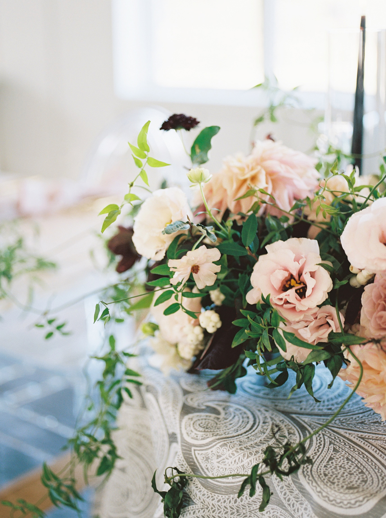Low floral arrangement of blush, mauve, and ivory blooms accented by dark green and black foliage