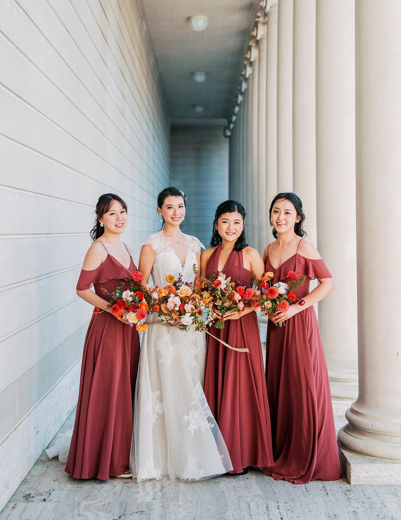 bride posing with bridesmaids cinnamon rose dresses