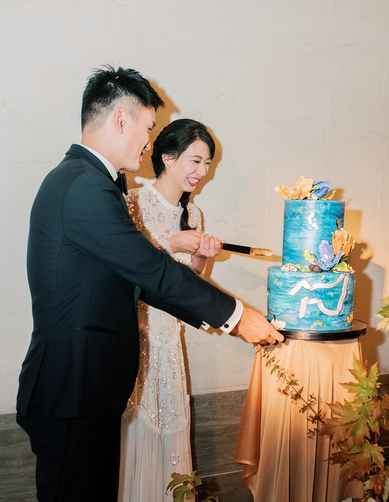 bride groom cutting blue two-tier wedding cake