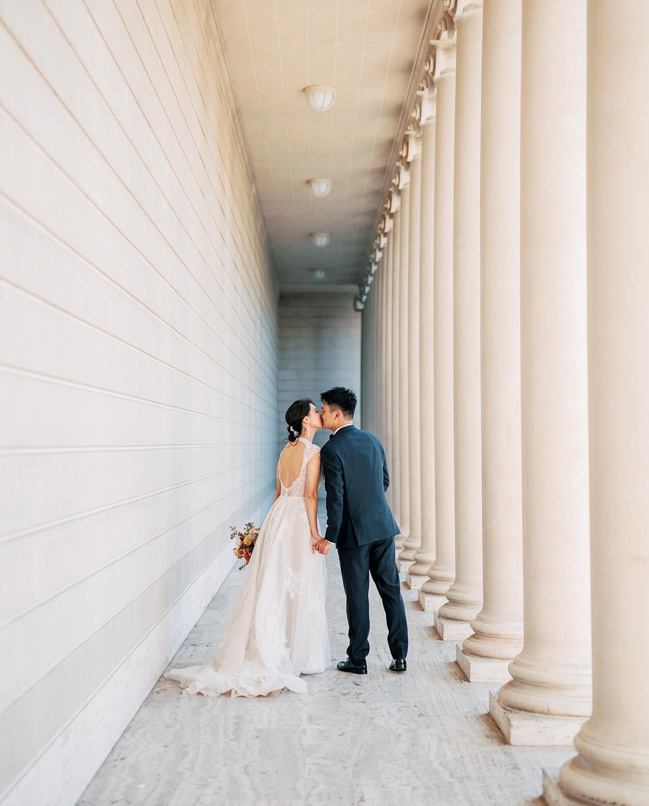 wedding couple kiss near museum pillars