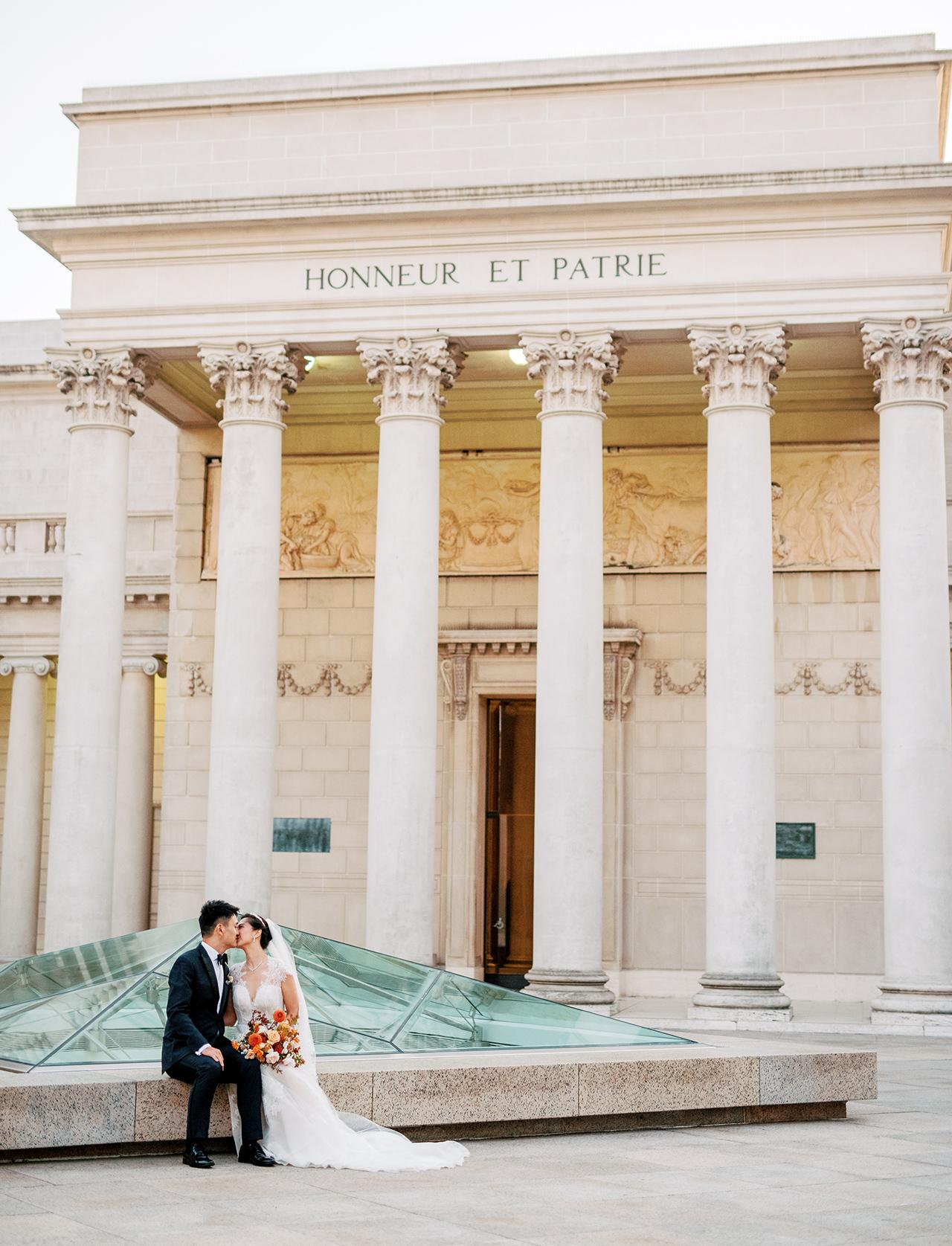 wedding couple kiss outside museum