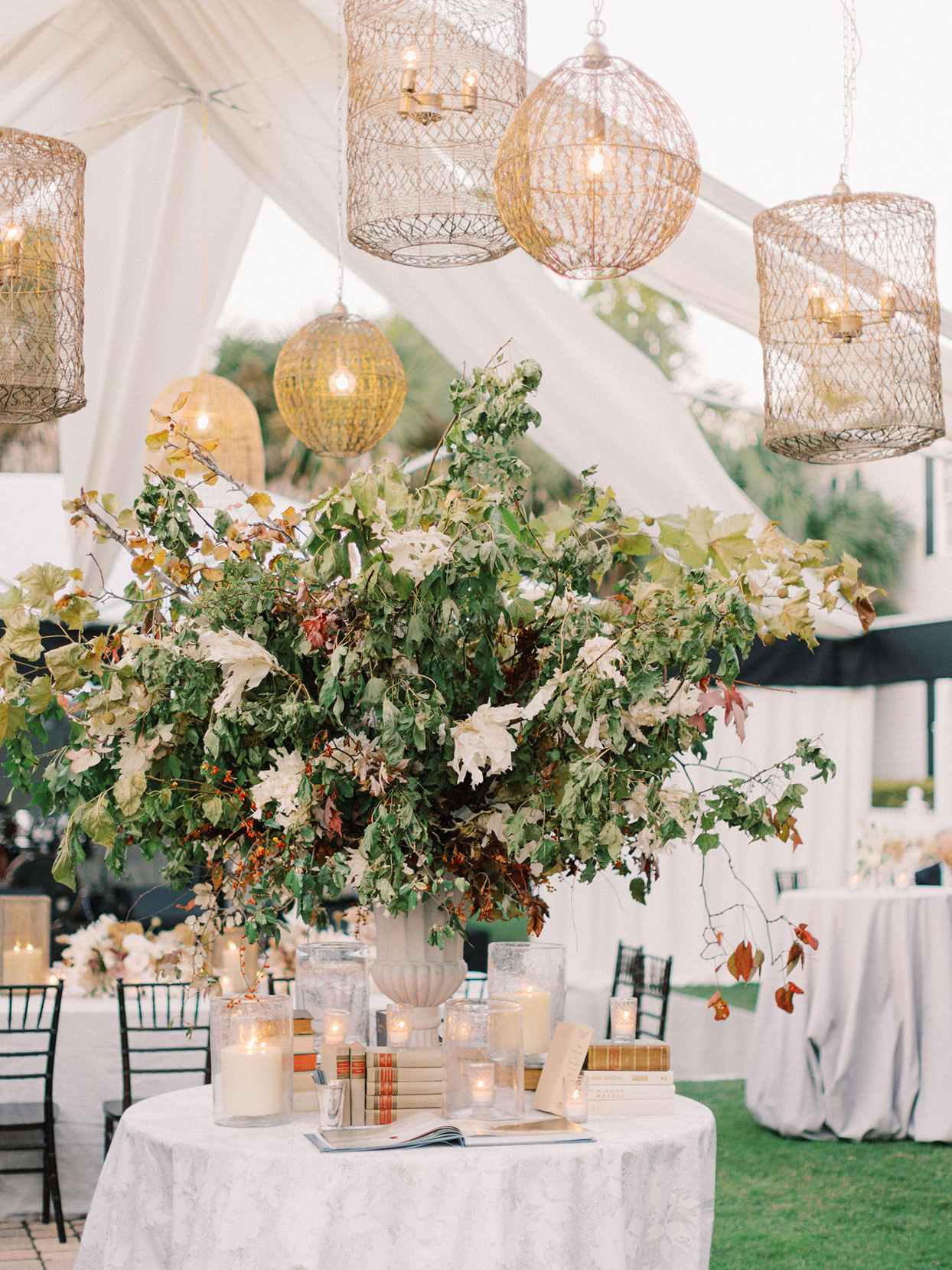 megan parking wedding reception guest book table in elegant tent with hanging lanterns