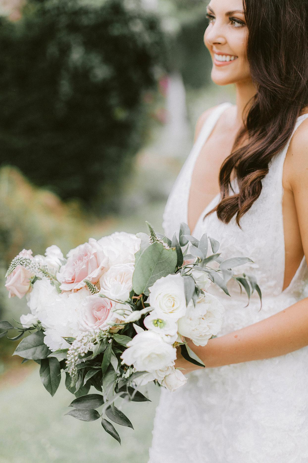 bride holding pastel floral wedding bouquet