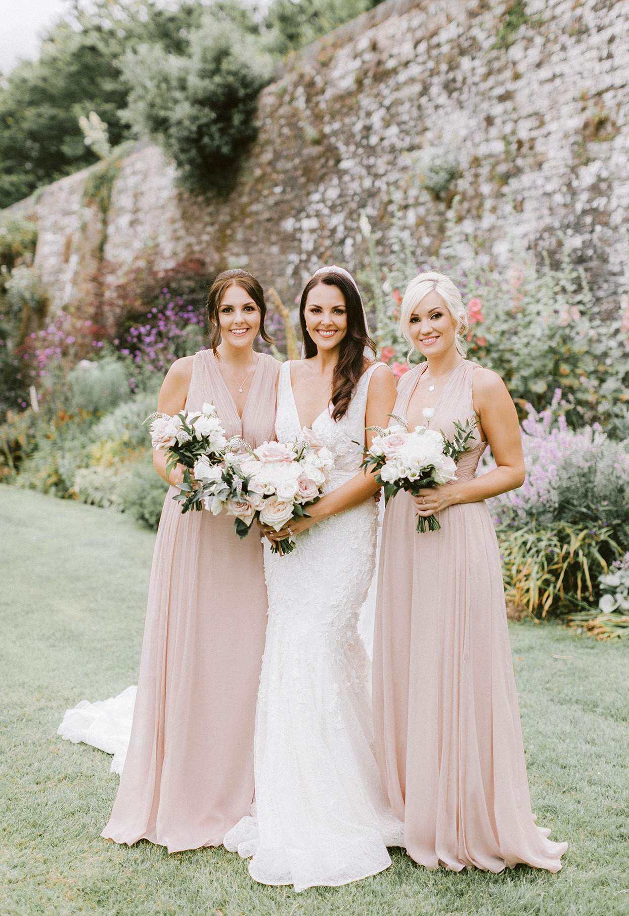 bride and bridesmaids in pastel pink standing on lawn