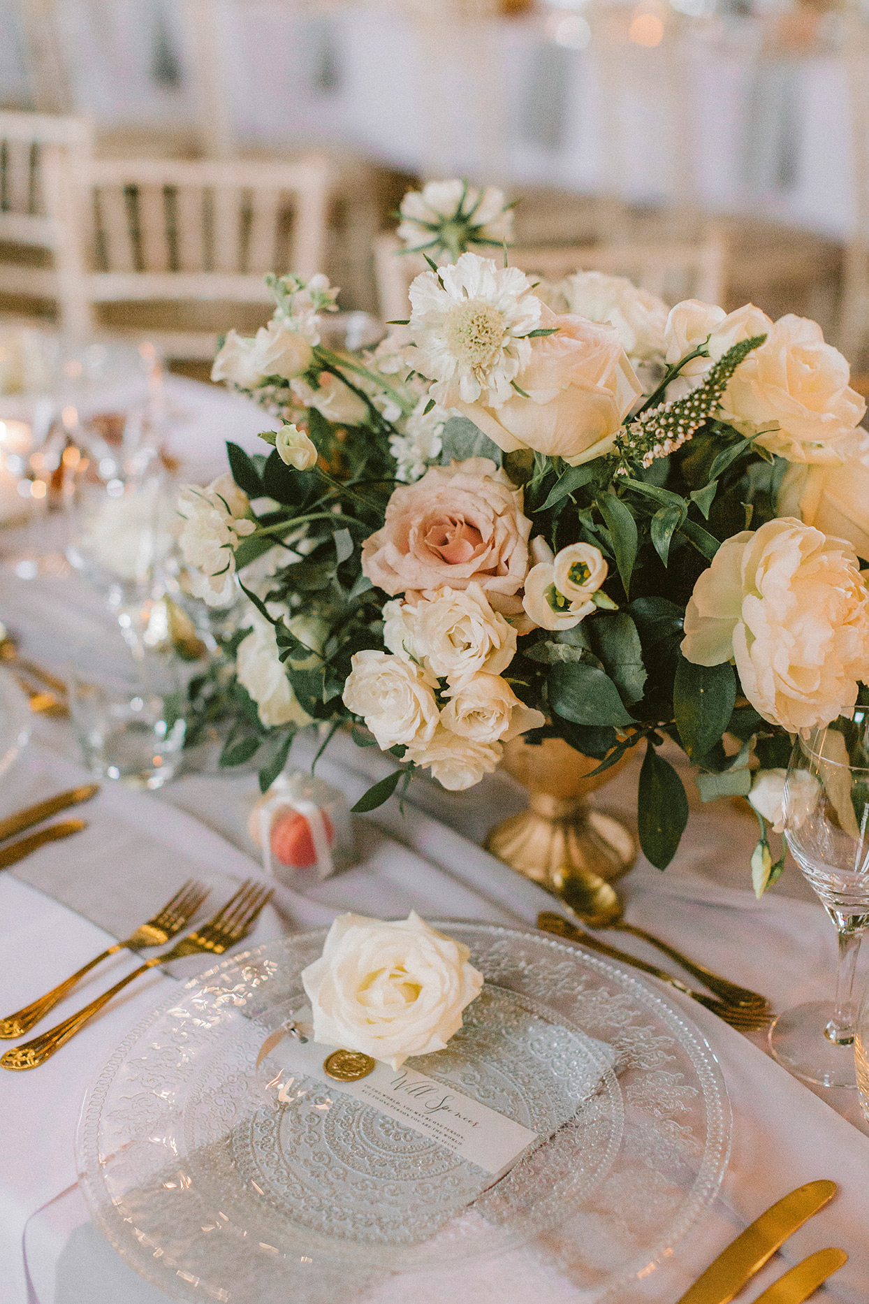 pastel floral centerpiece in gold vase on table